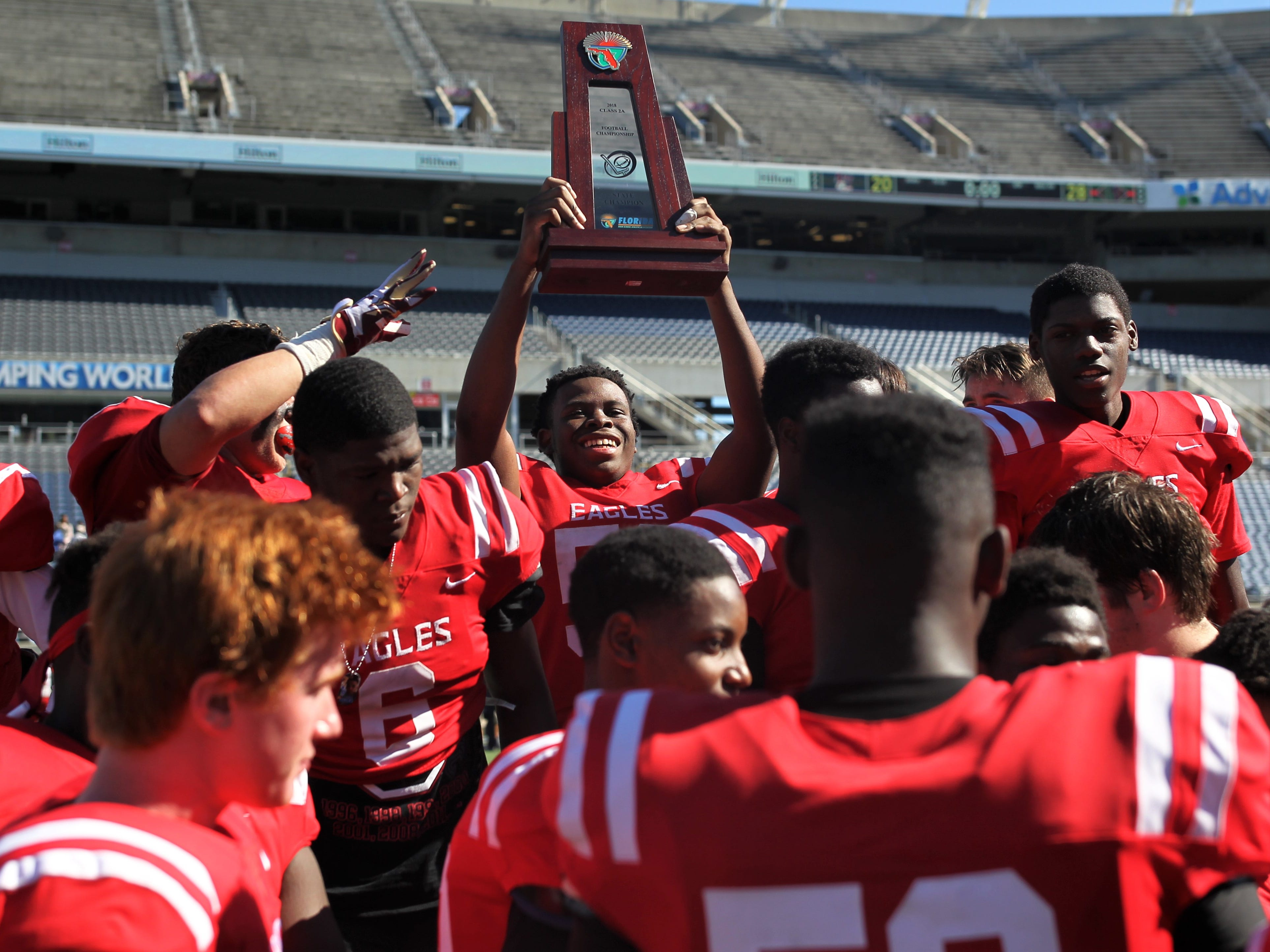 Elisha Partner celebrates with the trophy after NFC beat Champagnat Catholic 28-20 to win a Class 2A state championship on Friday, Dec. 7, 2018, at Orlando's Camping World Stadium.