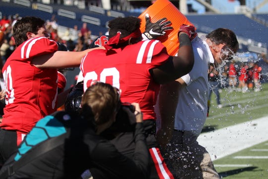 NFC head coach Steve Price gets a water bath as the Eagles beat Champagnat Catholic 28-20 in a Class 2A state championship game on Friday, Dec. 7, 2018, at Orlando's Camping World Stadium.