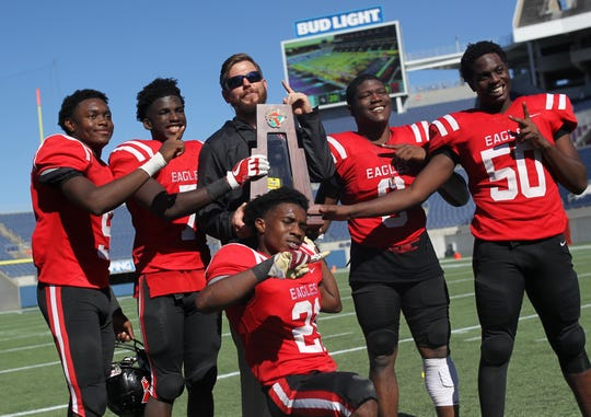 Deandrae McCray (9), T.J. Ward (7), Von Hayes (21), Quan Myrick (6), and Raymond Jackson (50) celebrate with defensive coordinator Jesse Braswell after NFC beat Champagnat Catholic 28-20 to win a Class 2A state championship on Friday, Dec. 7, 2018, at Orlando's Camping World Stadium.