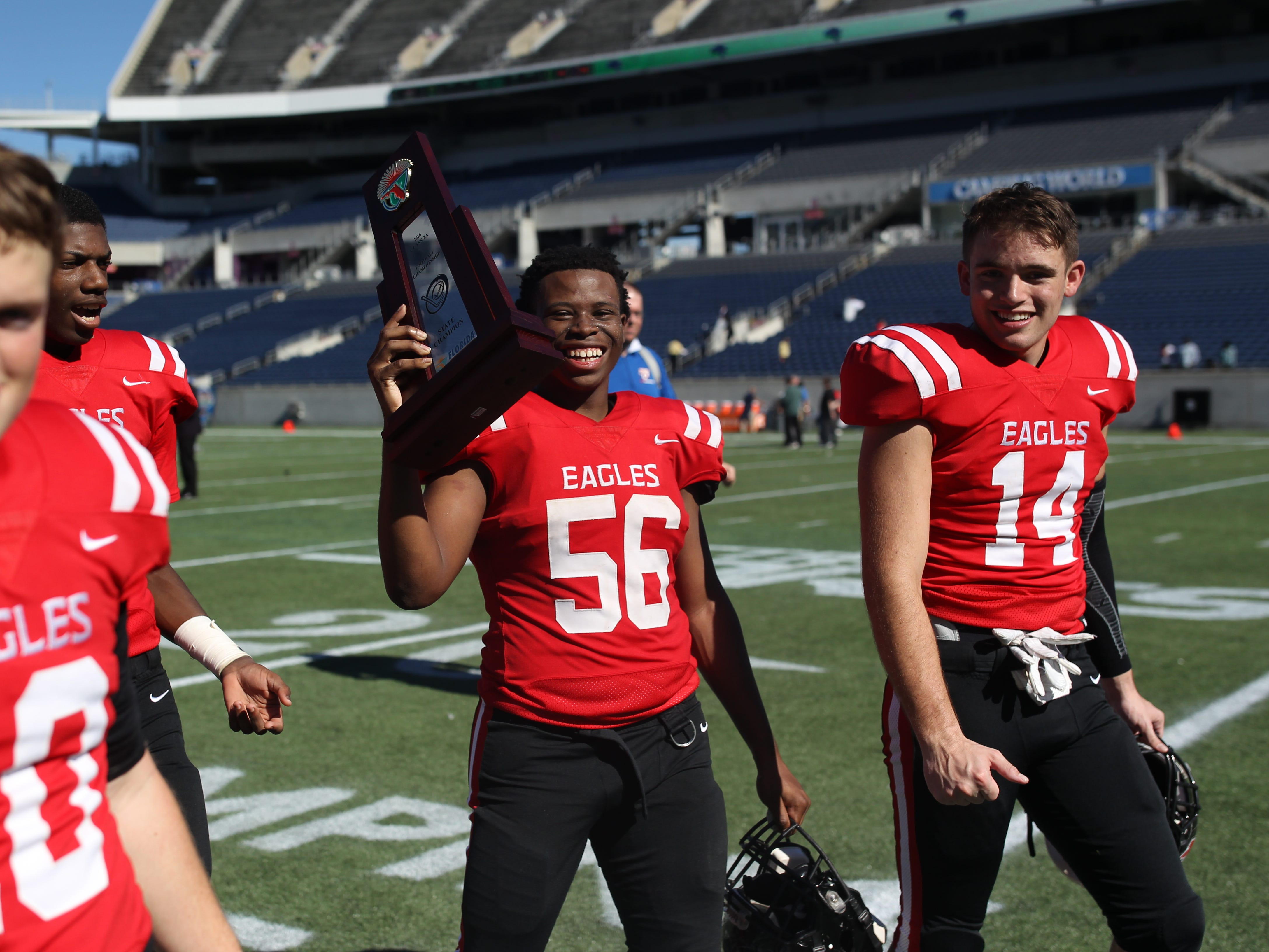 Elisha Partner (56) and Nick Molk (14) celebrate after NFC beat Champagnat Catholic 28-20 to win a Class 2A state championship on Friday, Dec. 7, 2018, at Orlando's Camping World Stadium.