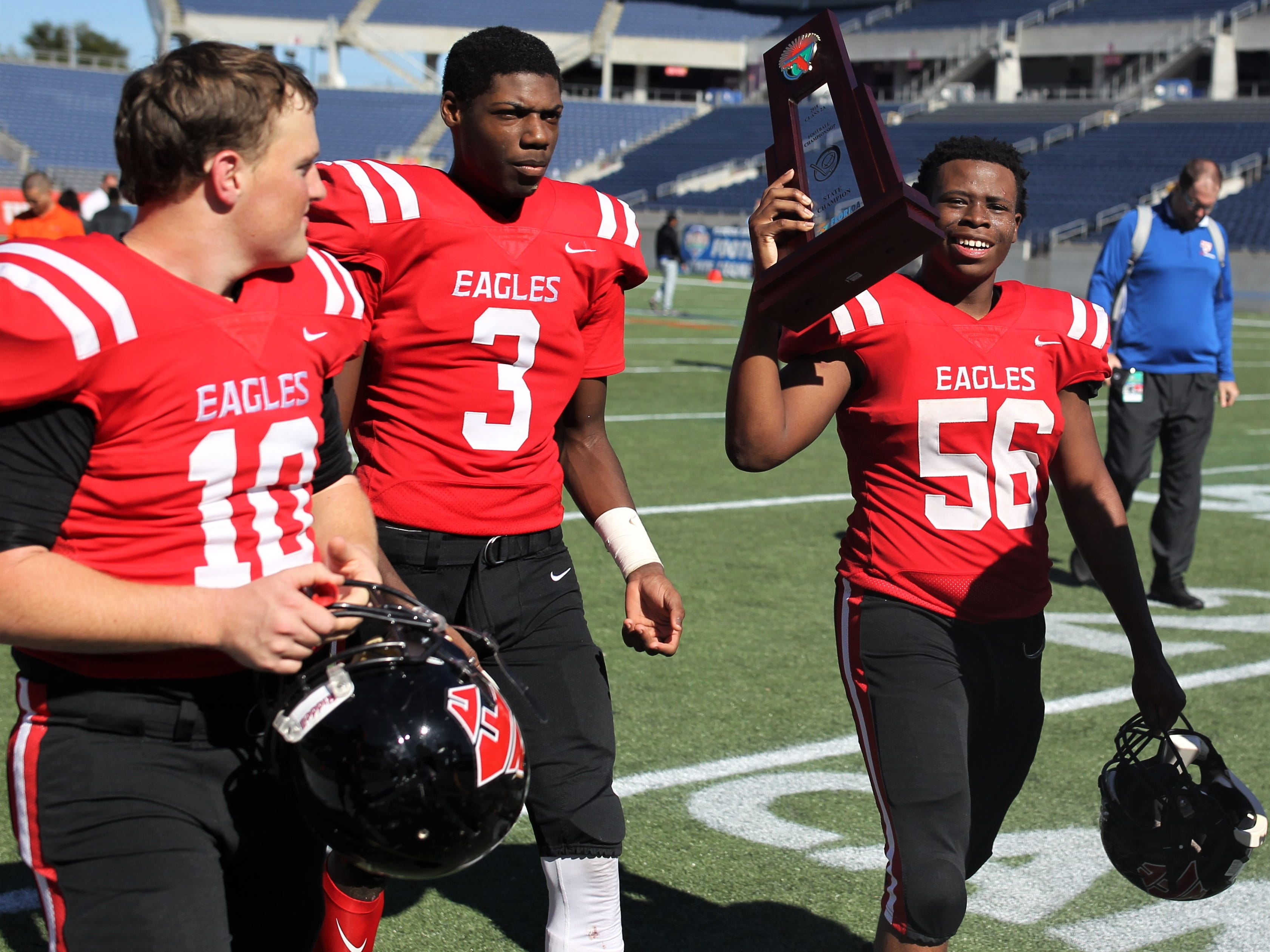 Elisha Partner (56), Tredarious Langston (3), and Chandler Gwartney (10) celebrate after NFC beat Champagnat Catholic 28-20 to win a Class 2A state championship on Friday, Dec. 7, 2018, at Orlando's Camping World Stadium.