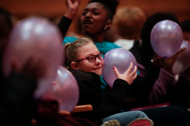 """Shiloh Loehrer, a W.T. Moore third grader, listens to sound vibrations in a balloon at the direction of 'America's Got Talent' star Mandy Harvey as she taught W.T. Moore Elementary and Swift Creek Middle school students about the connection between sound waves and vibrations in Opperman Music Hall at Florida State University as part of """"Opening Nights in Class"""" Friday, Dec. 7, 2018."""
