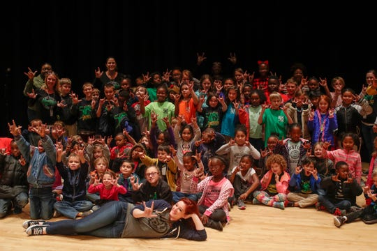 """W.T. Moore Elementary and Swift Creek Middle students sign """"I love you"""" as they pose for a photo with 'America's Got Talent' star Mandy Harvey after she taught them about the connection between sound waves and vibrations in music as part of the """"Opening Nights in Class"""" educational program at Florida State University Friday, Dec. 7, 2018."""