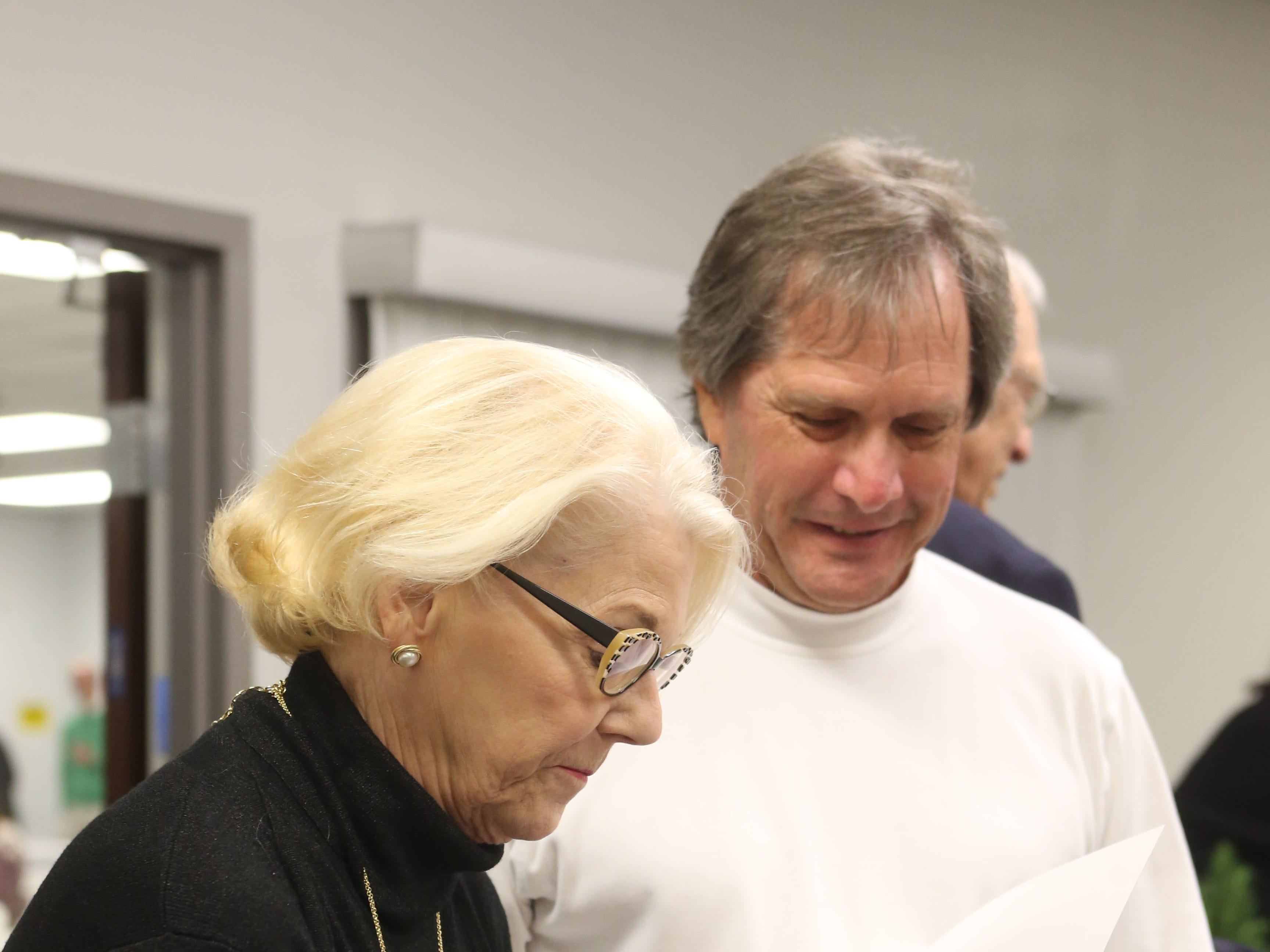 Sally Karioth, wife of Gerald Ensley, signs a book at a launch party held at the Tallahassee Democrat for Gerald Ensley's book, 'We Found Paradise,' Thursday, Dec. 6, 2018.