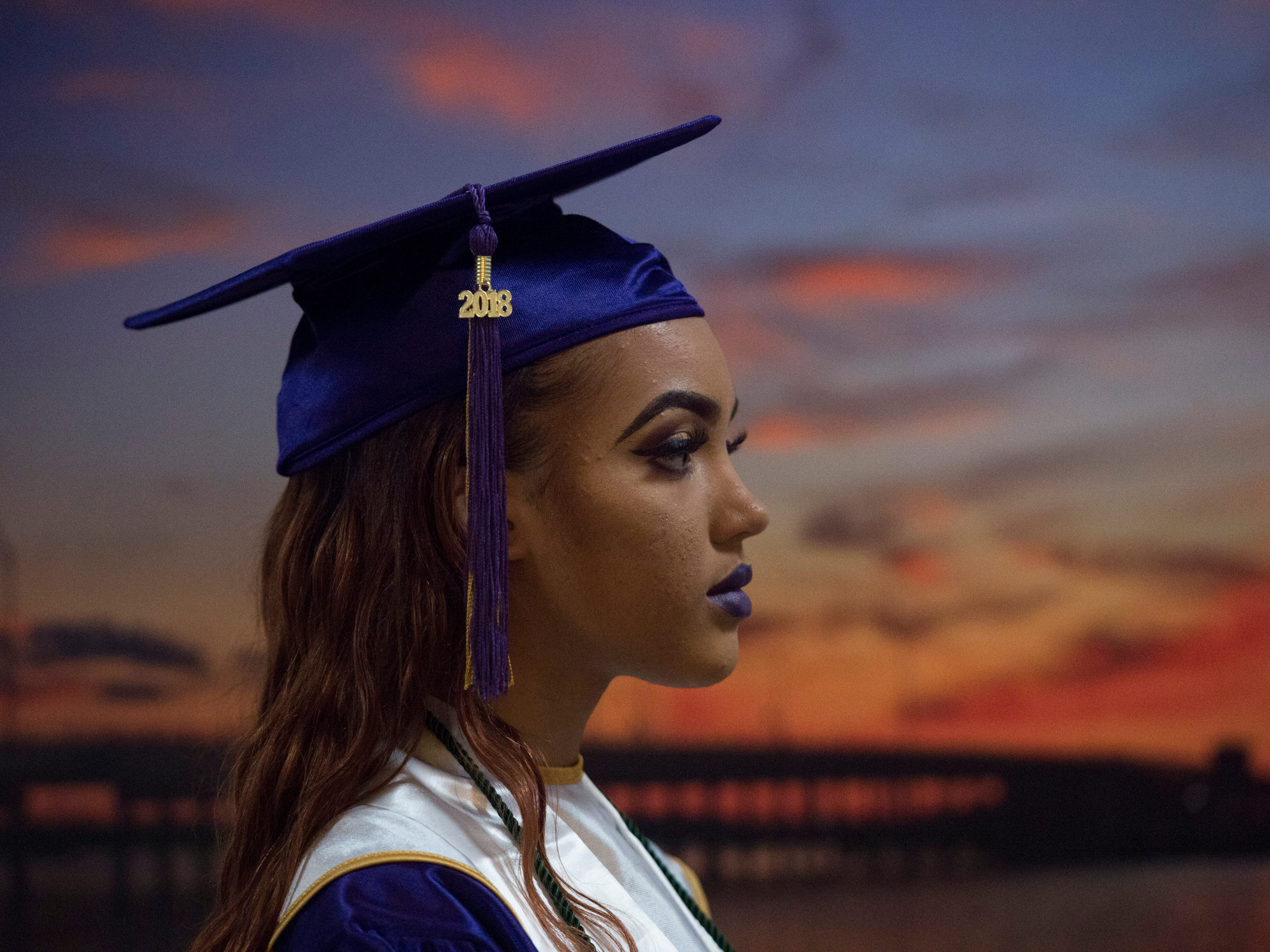 """""""I'm excited to get it done,"""" said Fort Pierce Central High School graduate Olivia Atandi, 18, of Port St. Lucie, standing in front of an image of a Fort Pierce sunset ahead of the school's 2018 commencement ceremony May 25, 2018, at the Havert L. Fenn Center in Fort Pierce. Because of flooding, the commencement was moved from the St. Lucie County Fairgrounds and split into two ceremonies Friday."""