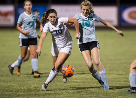 Martin County's Neve Duston (left) and Jensen Beach's Alexis Monroe-McMath vie for the ball during the first half of the high school girls soccer game Thursday, Dec. 6, 2018, at Jensen Beach High School.