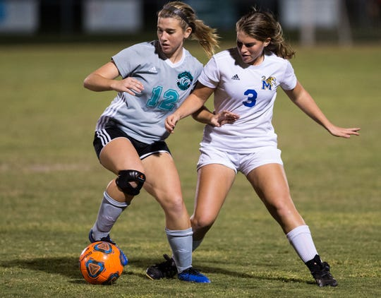 Jensen Beach's Emily Phillips (left) keeps the ball away from Martin County's Jordyn Plewke during the second half of the high school girls soccer game Thursday, Dec. 6, 2018, at Jensen Beach High School.