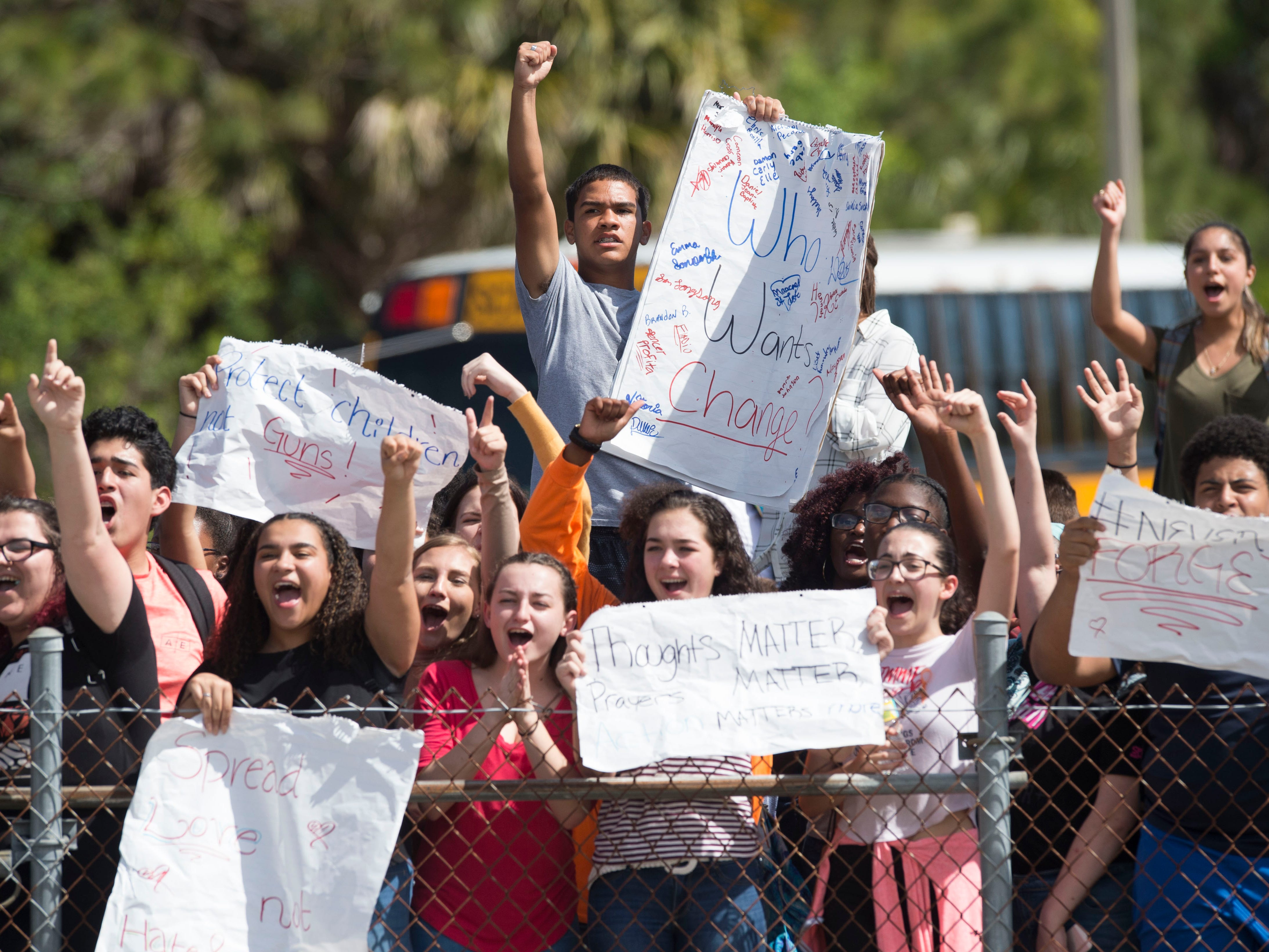 """""""I'm protesting about gun control,"""" said Jonathan Geronimo (center), 15, a Port St. Lucie sophomore, after he and about 100 other Port St. Lucie High School students react to a honking car at the front gates of the school during a peaceful protest honoring the 17 slain Marjory Stoneman Douglas High School students on Feb. 21, 2018 at the school in Port St. Lucie."""