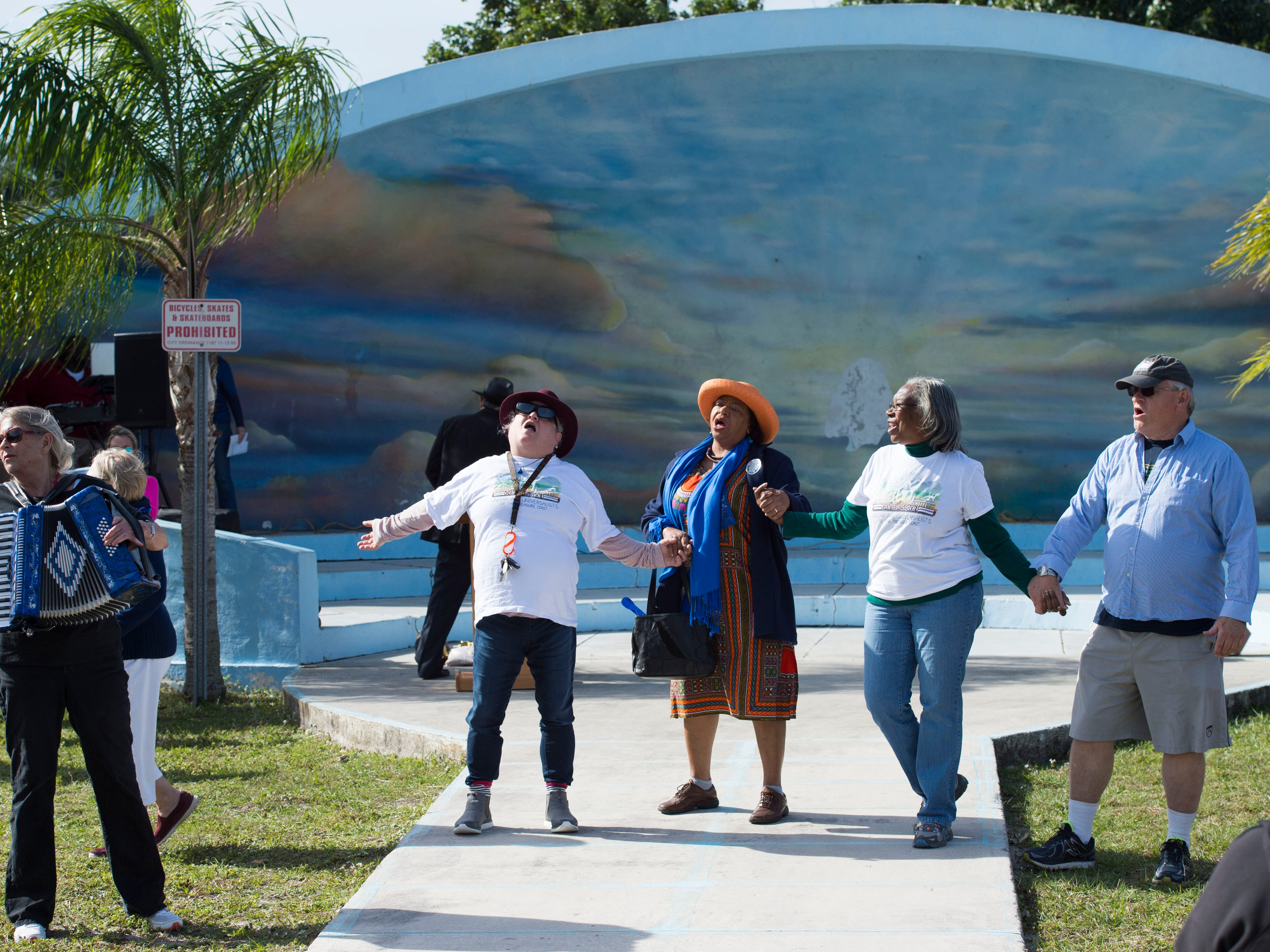 """Led by the Treasure Coast Unitarian Universalist Congregation music director Jackie May (from left), Carolyn Haykin, of Jensen Beach, Stuart commissioner Eula Clarke, Barney Miller Moore, of Port St. Lucie and Fred Fiske, seasonal resident of Stuart, join hands and sing """"We Shall Overcome"""" on Jan. 15, 2018 at East Stuart Partnership's Martin Luther King Jr. celebration at Memorial Park in Stuart. """"This is my 40th Martin Luther King Jr. parade playing accordion,"""" May said. """"I really believe in bringing the music."""" The celebration began with a parade through East Stuart and concluded with the festival that included speakers, performances, food and more."""
