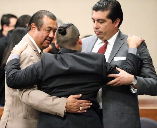 Reniery Adalberto Galeano, center, turns to hug his attorneys, Sergio Saldivar, left, and Leonardo Maldonado after he was acquitted of the charge of aggravated assault with a deadly weapon Thursday in 168th District Court.