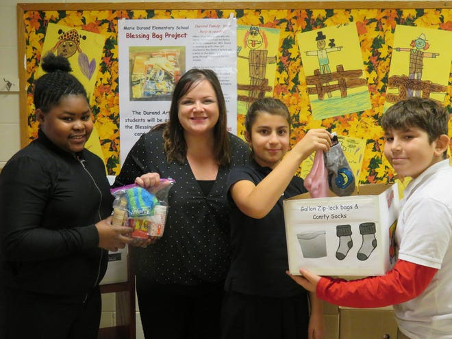 Students from Marie Durand Elementary School, who helped with the Blessings Bag Project, present their donations to Jami Denigris, director of Oncology Services at the Frank and Edith Scarpa Regional Cancer Pavilion in Vineland.