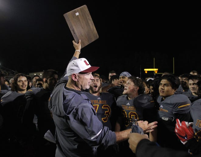 Tulare Union coach Darren Bennett with the championship trophy after the win against Righetti in Tulare, Calif., Friday, Nov. 23, 2018.
