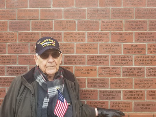 WWII veteran Vito Mastrangelo stands beside the break bearing his name at the Greatest General Mural. Mastrangelo worked to clear the remains of thousands of deceased soldiers on D-Day.