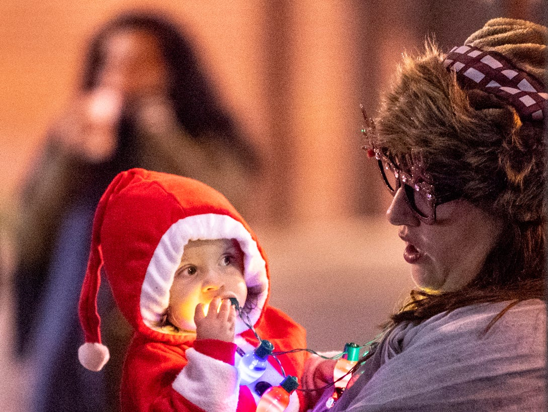 Hunter Wilson plays with lights in the arms of his mother Staci Wilson during the Tulare Children's Christmas Parade and Tree Lighting on Thursday, December 6, 2018.