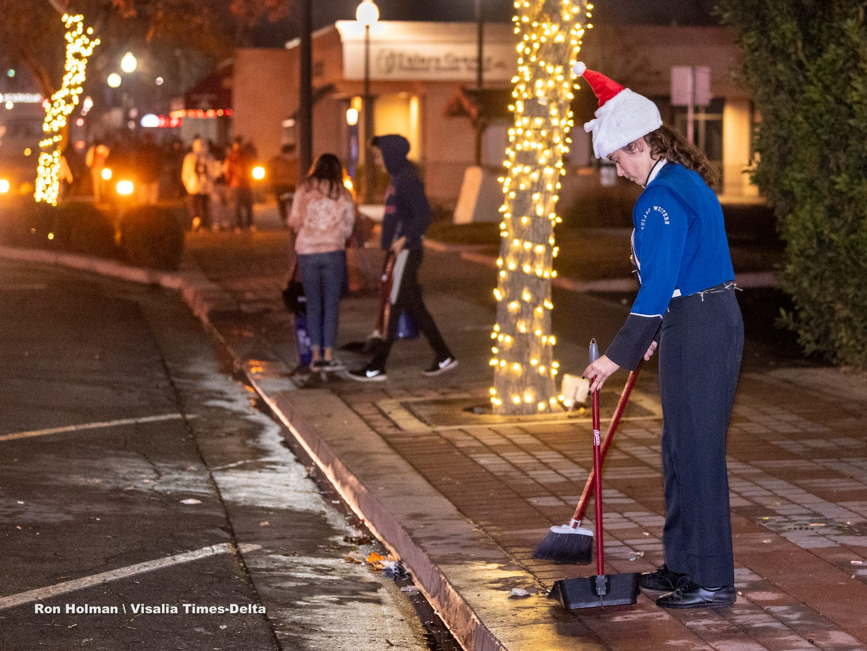 Tulare Western student Meia Borreli and others from her cross country team clean up after the Tulare Children's Christmas Parade and Tree Lighting on Thursday, December 6, 2018. The Chamber of Commerce made a donation to the team for their community service.