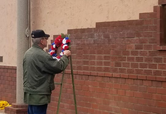 Vietnam veteran Jose Marquez places a memorial wreath, honoring those who lost their lives on Dec. 7, 1941.