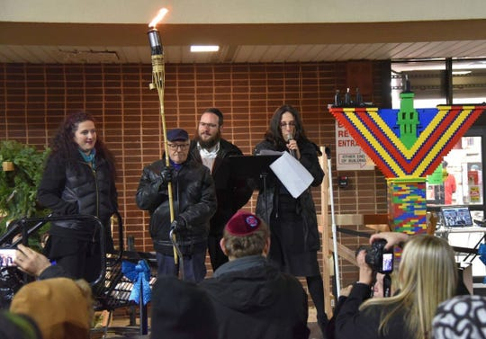 Michael Marder, 93, center, a Holocaust survivor of nine concentration camps, holds the flame to light the holiday menorah at ShopRite of Tallman on Wednesday.