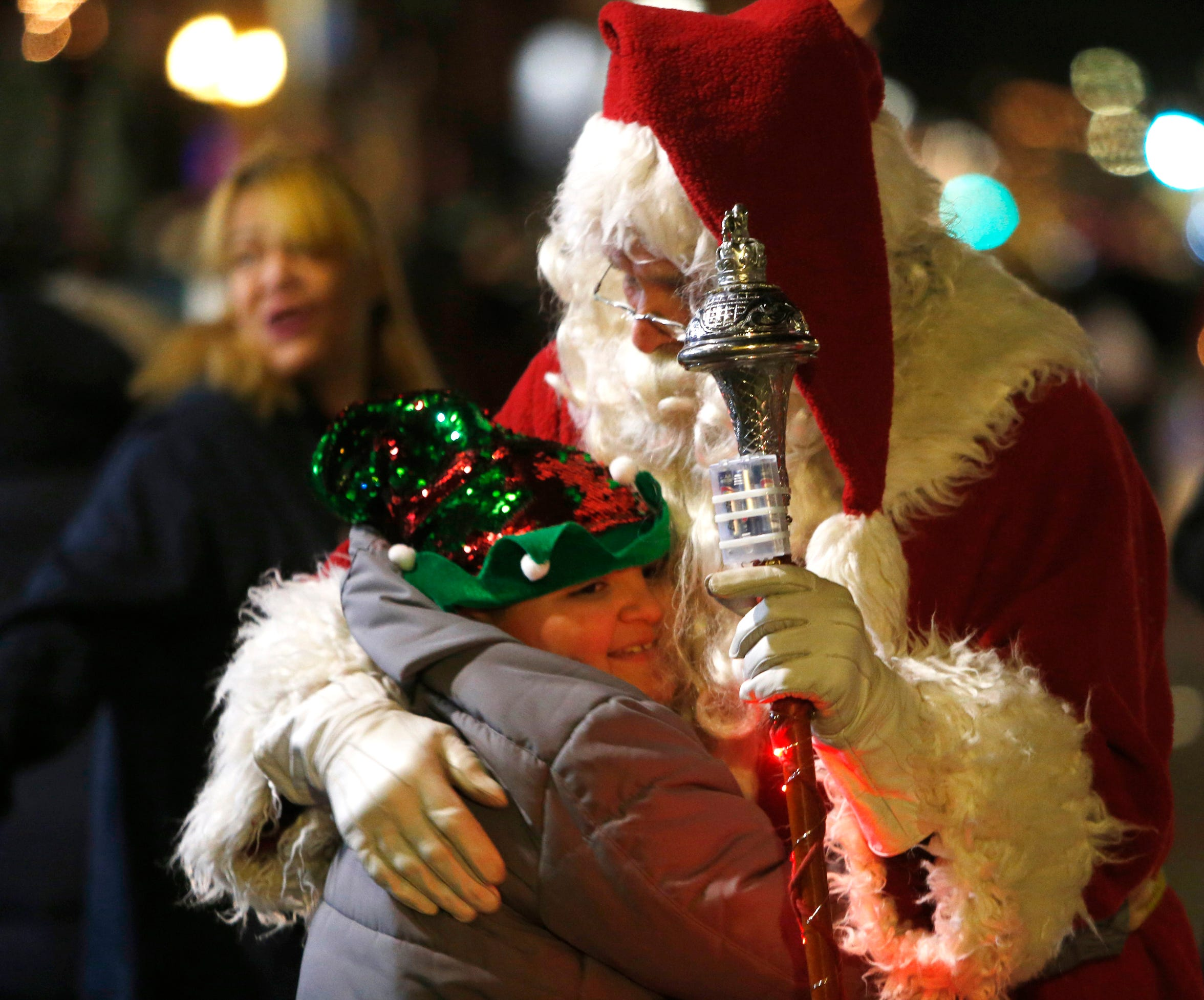 Willie Melton III gives a hug to Santa Claus, Bill Tomkins of the Amerscot Highland Pipe Band during the Celebration of Lights Parade in the City of Poughkeepsie on November 30, 2018.