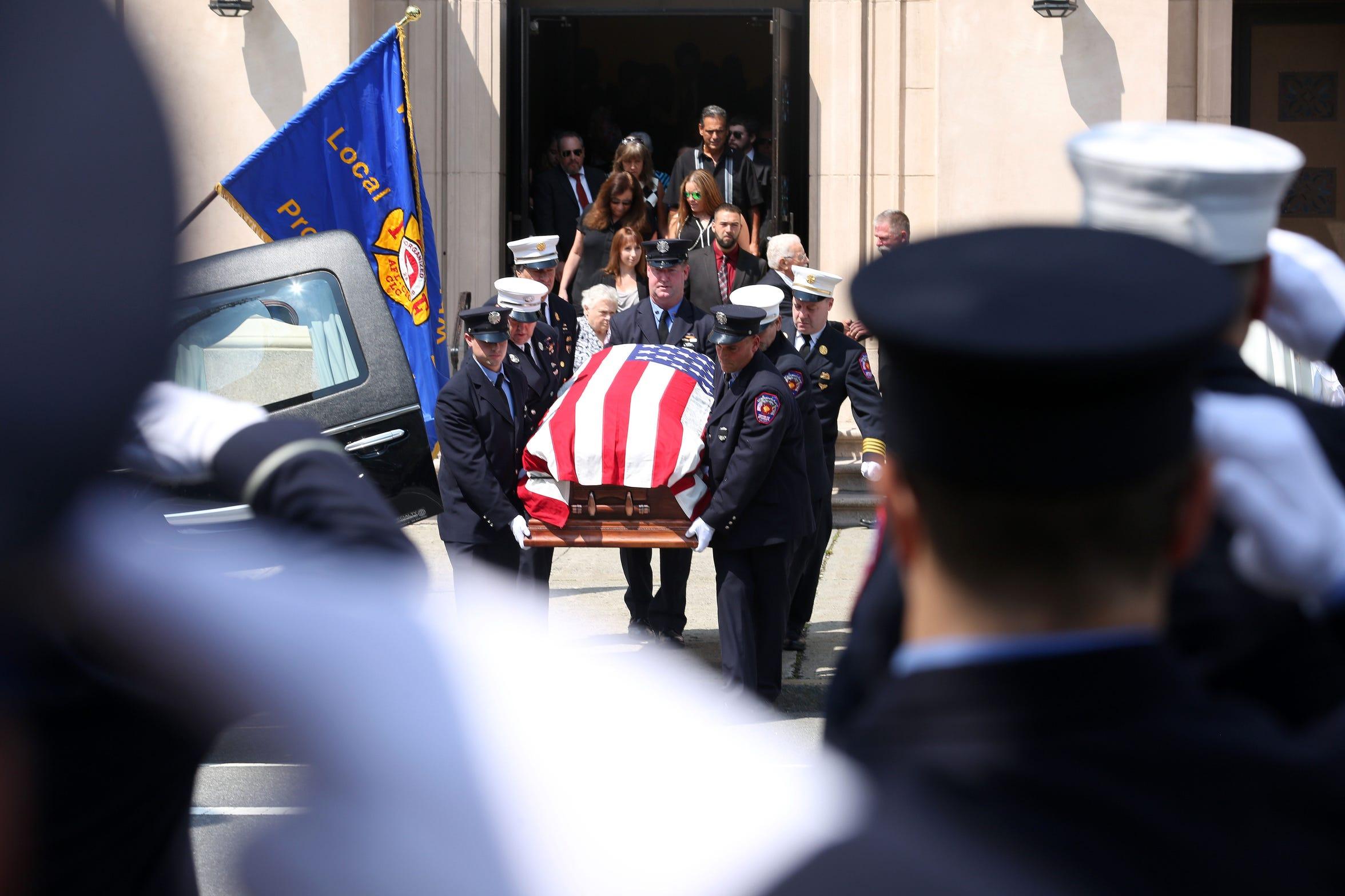 White Plains firefighters carry the flag draped coffin of Lt. Clark Douglass out of  Mount Carmel Church following his funeral mass July 27, 2018. Douglass died earlier this week from a 9-11 related cancer.