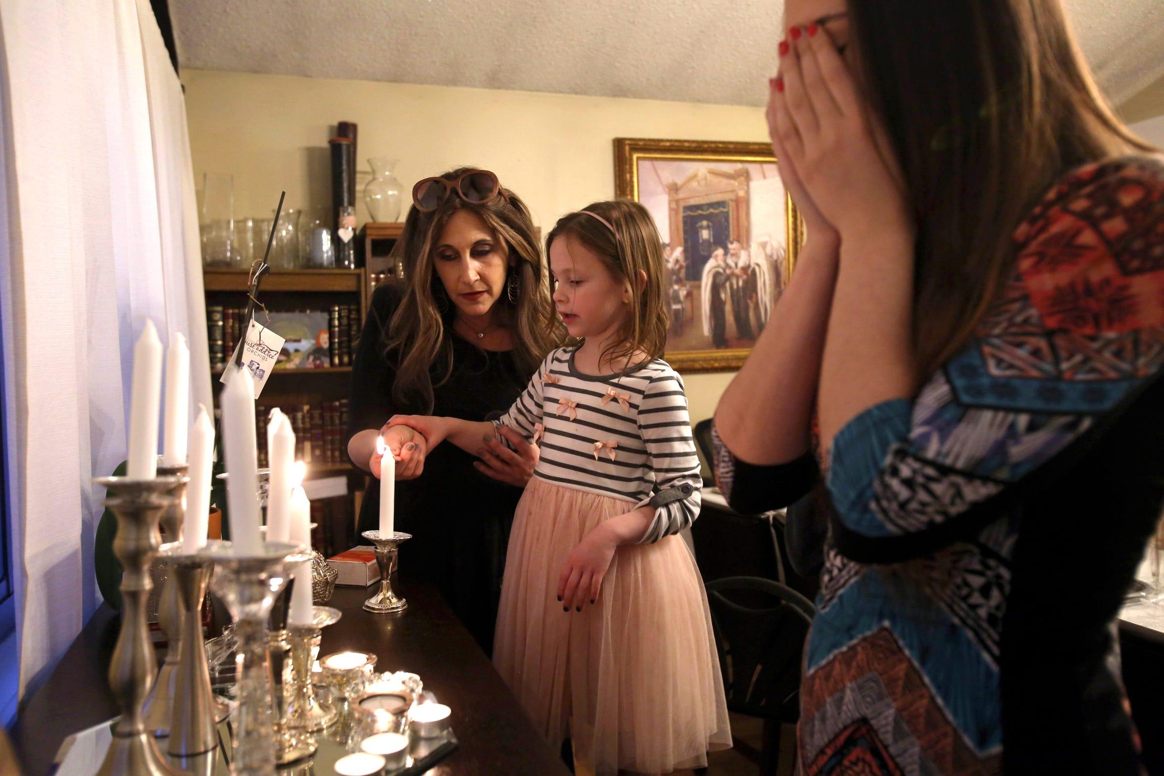 Bassie Friedman helps her daughter Devorah Leah Friedman, 6, light a candle during Shabbos as her son's girlfriend, Miriam Mitzman, recites a blessing Feb. 16, 2018 in Pomona.