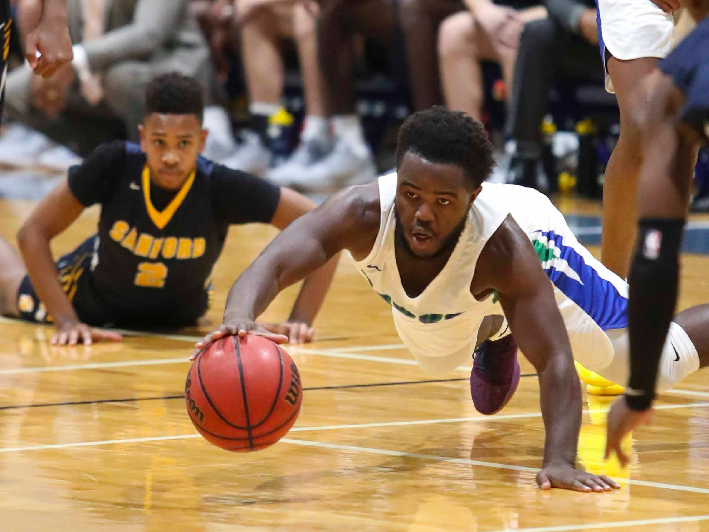 St. Georges' Tyrese Owens dives for a loose ball after battling with Sanford's Corey Perkins (left) during Sanford's 62-56 overtime win at St. Georges Thursday.