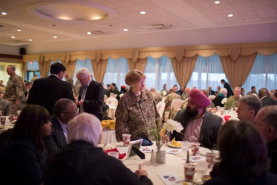 Delaware Air National Guard Adjutant General Carol Timmons (center left) speaks with  Charanjeet Singh Minhas of the Delaware Sikh Awareness Coalition at a Thanksgiving prayer breakfast.