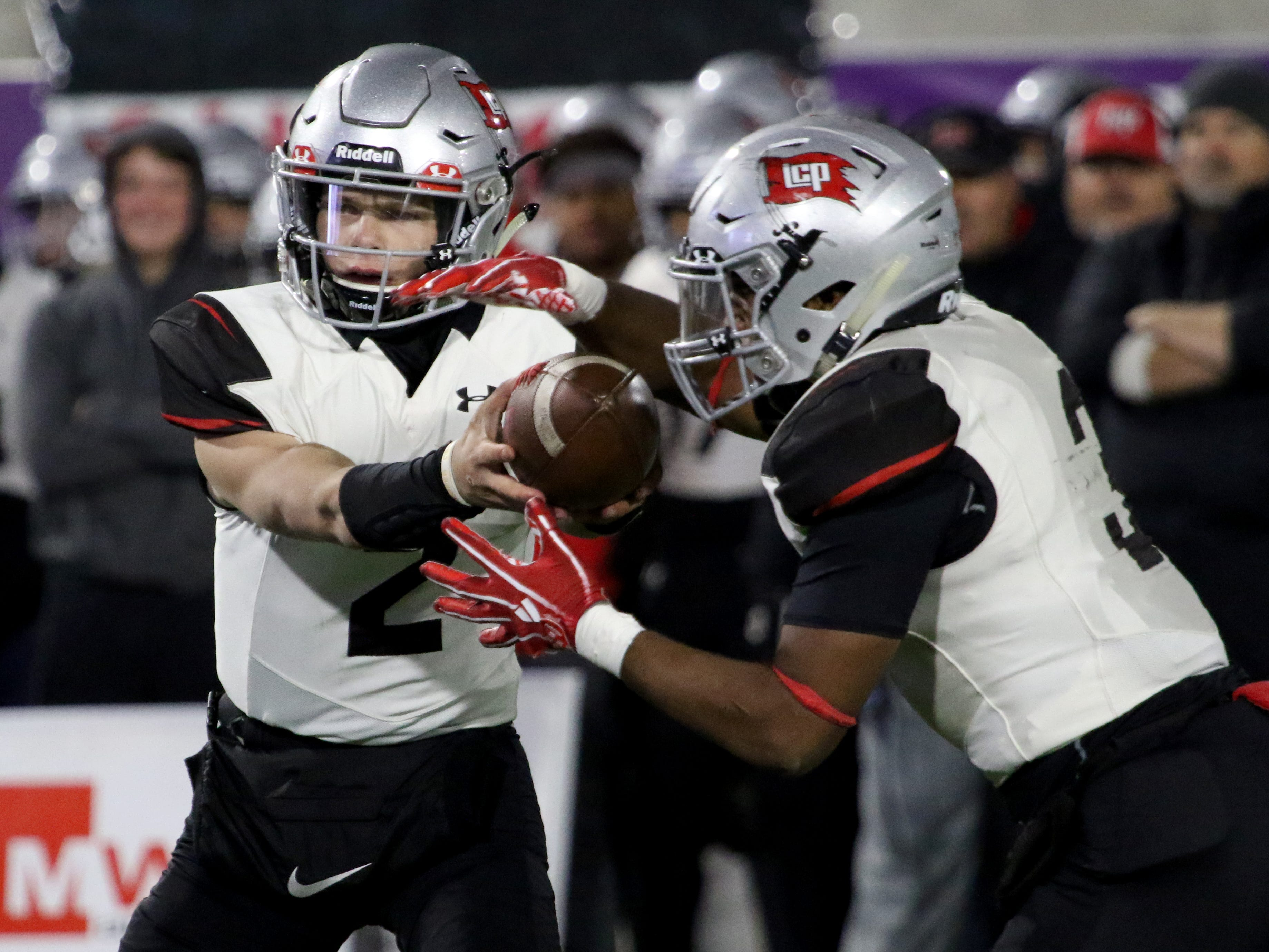 Lubbock Cooper's Brenden Mehl hands the ball off to Isaiah Johnson in the game against Rider Thursday, Dec. 6, 2018, at Wildcat Stadium in Abilene.