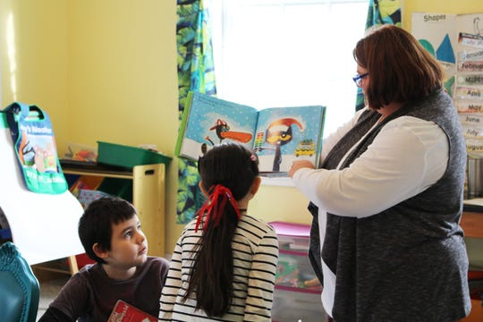 Jamie Block reads a book to the younger students at the C.A.S.S.-M.I.N.D. Academy.