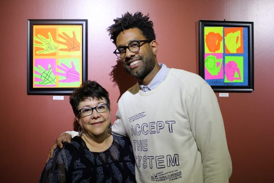 Nathaniel McDonald and Cindy Henceroth, the social worker and art therapist at the C.A.S.S.-M.I.N.D. Academy, pose with some of the students' art at Weasel Boy Brewing Company.