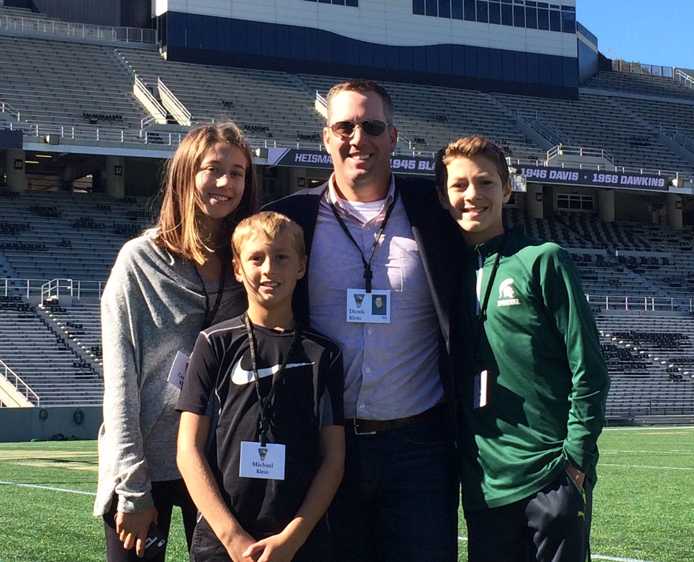 Former Army football player Derek Klein, second right, stands with his family on the field at Michie Stadium.