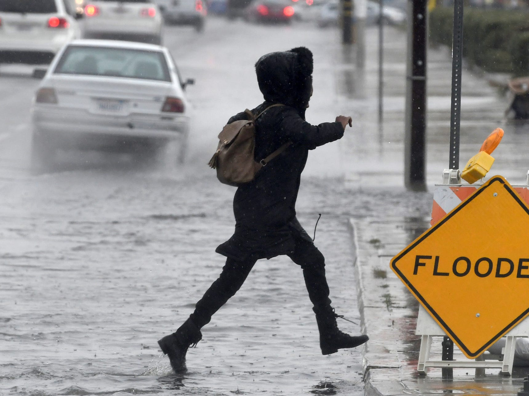A pedestrian leaps across a flooded portion of the La Paz and Seventh Street intersection as a winter storm arrived, Thursday, Dec. 6, 2018 in Victorville, Calif.