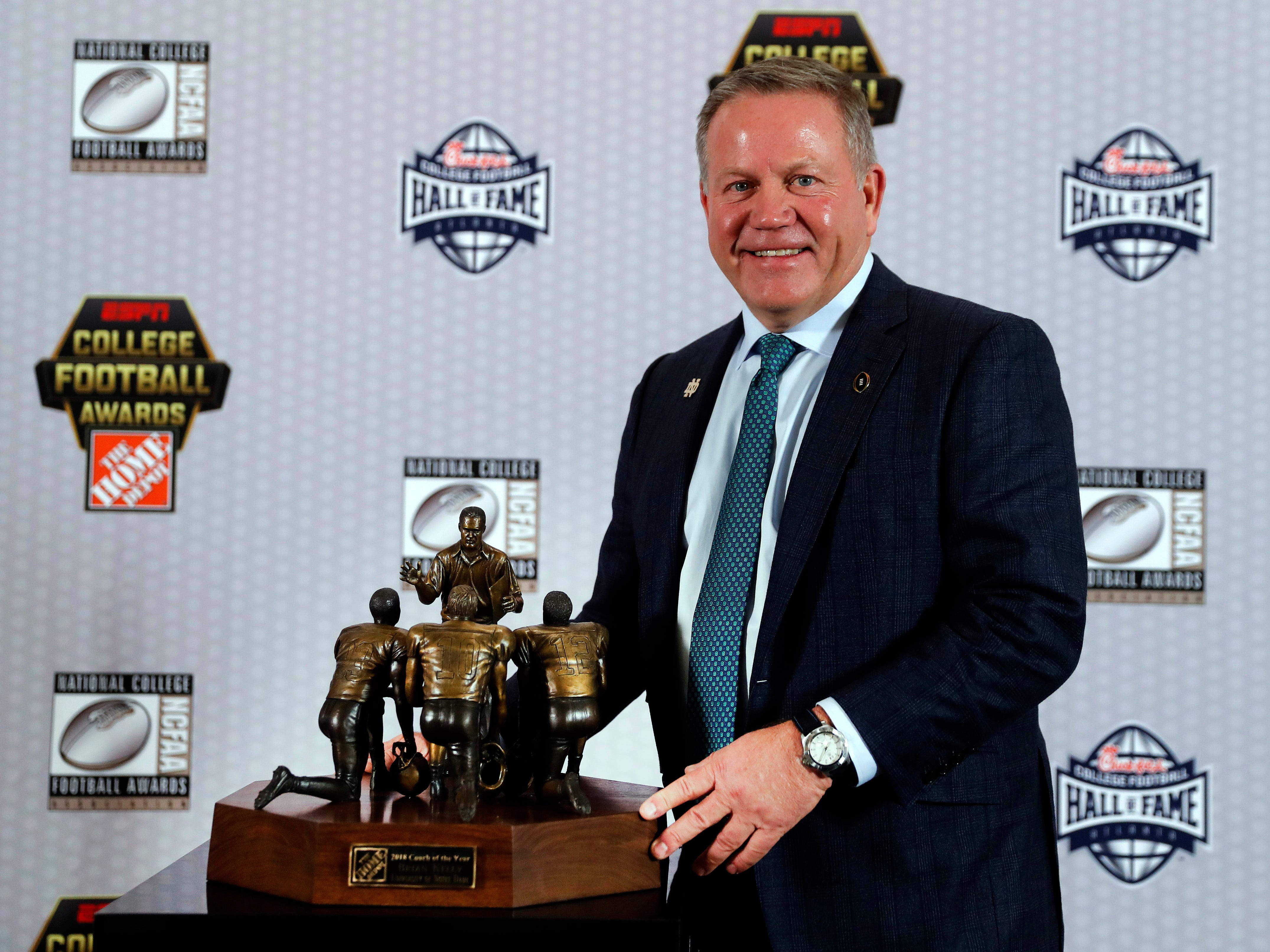 Notre Dame's Brian Kelly poses with the trophy after being named Coach of the Year.