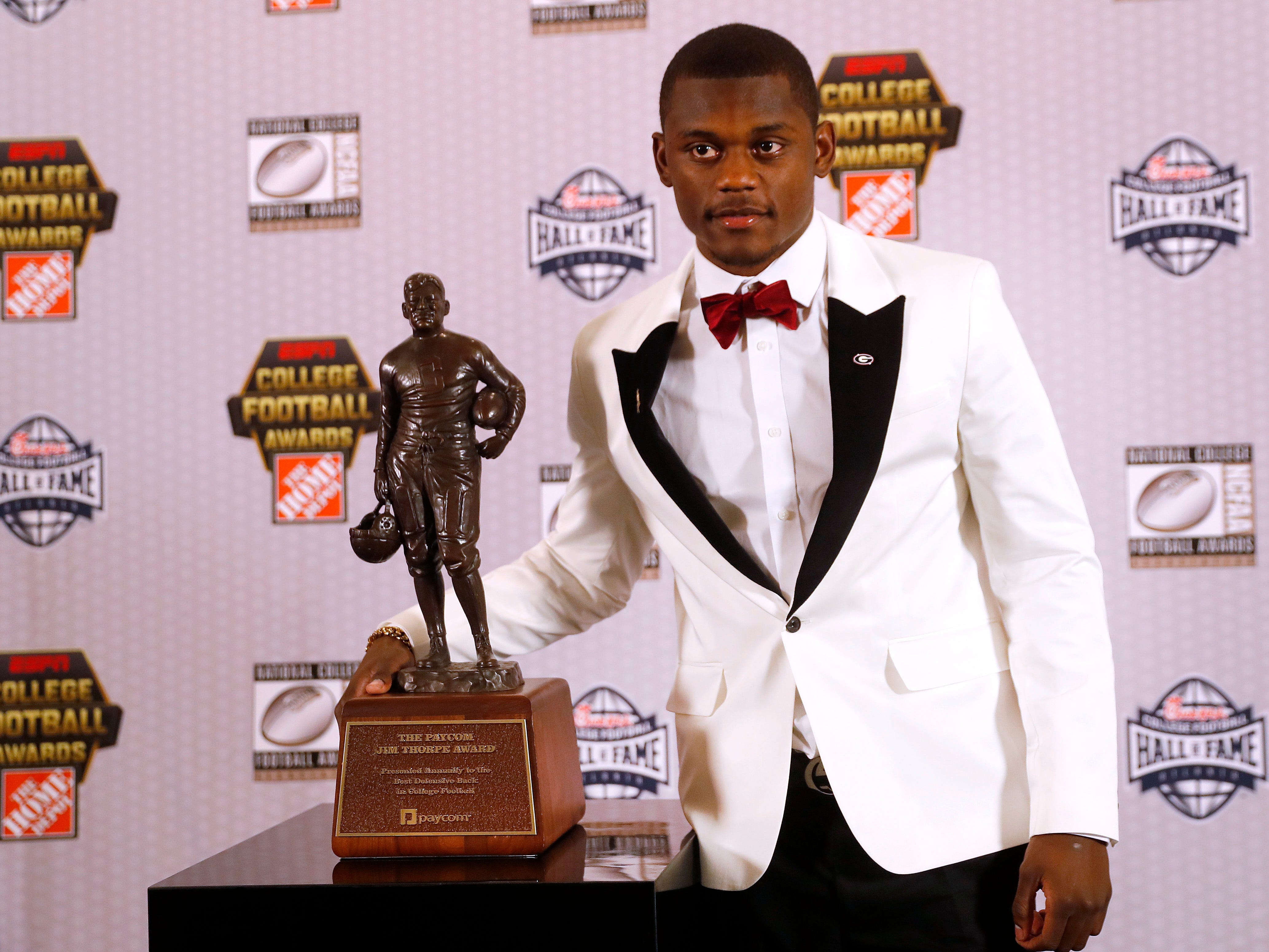 Georgia's Deandre Baker poses with the  Jim Thorpe Award as top defensive back in college football.