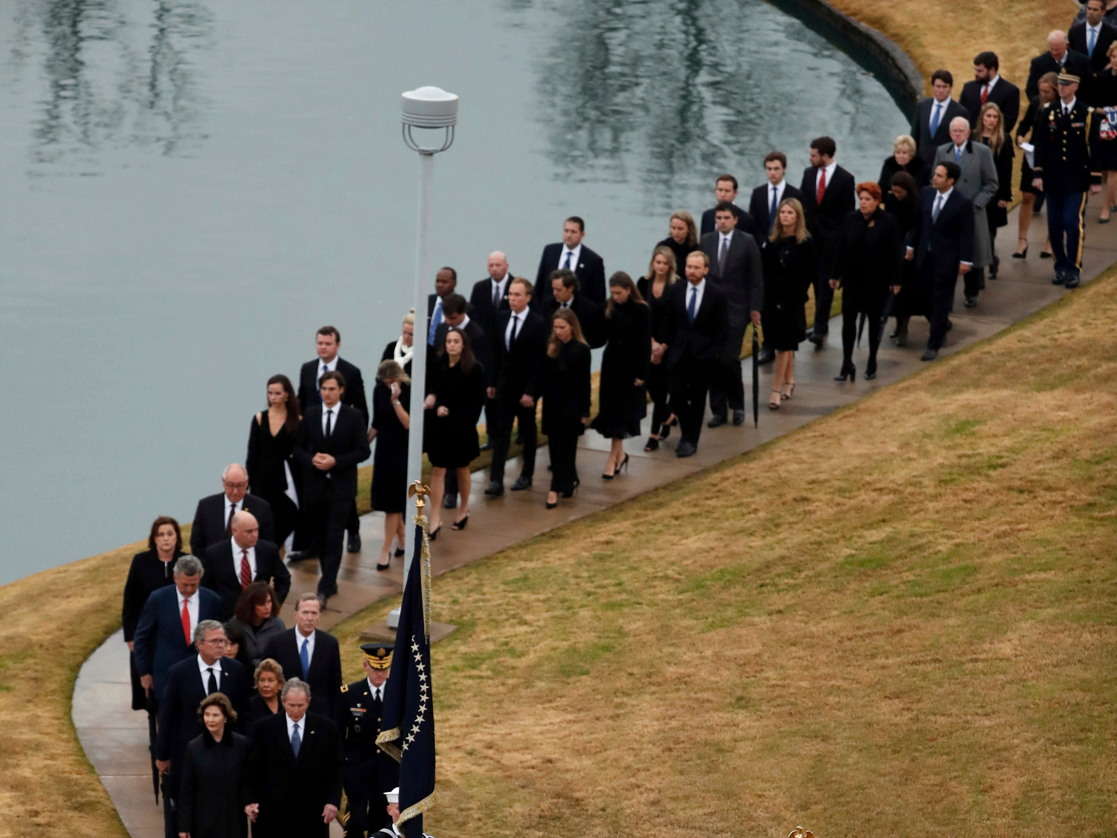 The flag-draped casket of former President George H.W. Bush is carried by a joint services military honor guard followed by family members the George H.W. Bush Presidential Library and Museum Thursday, Dec. 6, 2018, in College Station, Texas.