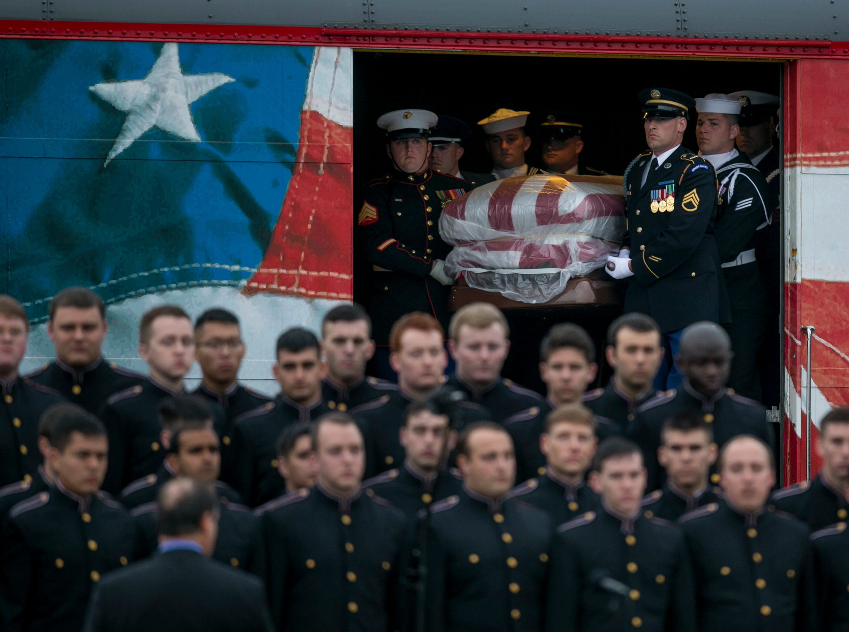 A joint military honor guard carries the casket of former President George H.W. Bush after it arrived by a presidential funeral train at Texas A&M University in College Station for burial at the George Bush Presidential Library on Thursday, Dec. 6, 2018.