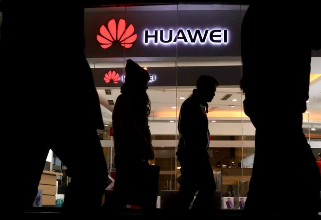 Pedestrians walk past a Huawei retail shop in Beijing on Dec. 6, 2018.