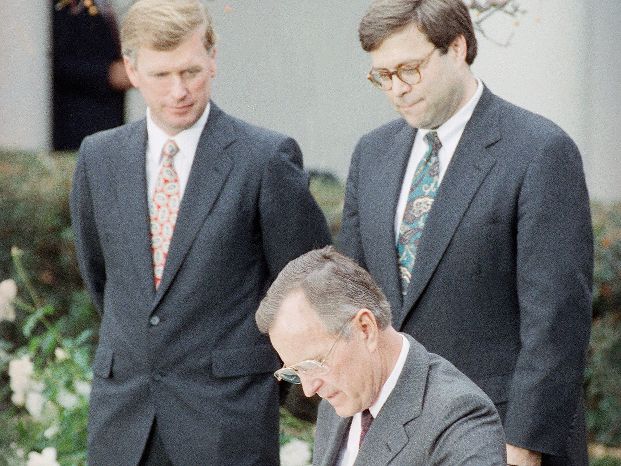 U.S. President George H. Bush signs into law new civil rights guarantees for women and minorities at a Rose Garden ceremony, Thursday, Nov. 21, 1991 in Washington, as Vice President Dan Quayle, left, and Acting Attorney General William Barr look on. The bill signing capped a two-year struggle with congress over whether the legislation encouraged job quotas. (AP Photo/Marcy Nighswander)