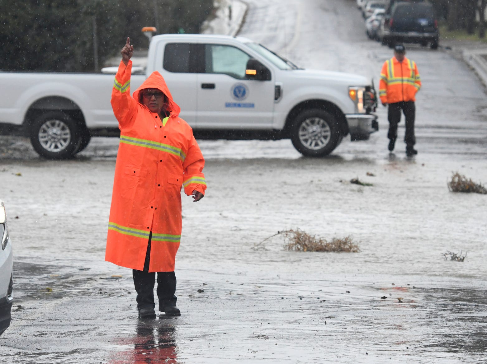 Victorville Public Works staff redirect traffic on Pebble Beach Drive as they closed the roadway due to flooding, Thursday, Dec. 6, 2018 in Victorville, Calif.
