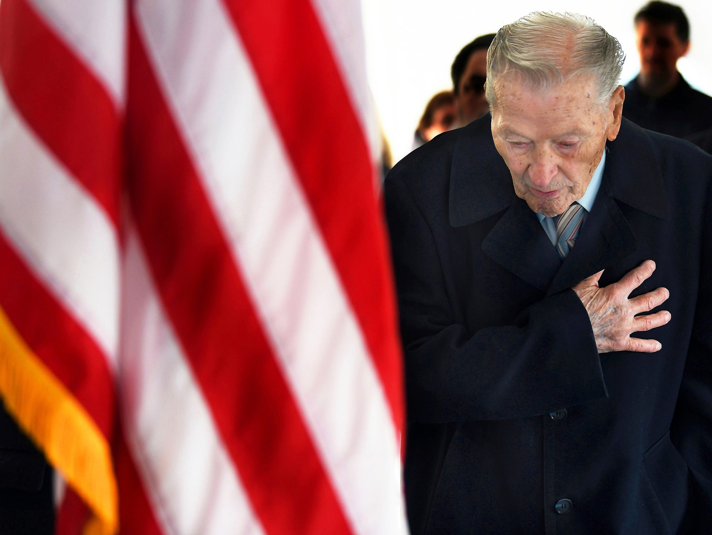 World War II veteran Walter A. Pasiak, 96, of Scranton, Pa., a survivor of the attack on Pearl Harbor on Dec. 7, 1941, bows his head and places his hand over his heart during the national anthem, Friday, Dec. 7, 2018, at a memorial ceremony recognizing the attack on Pearl Harbor held at the Lackawanna County Courthouse in downtown Scranton, Pa. Mr. Pasiak served in the U.S. Army.