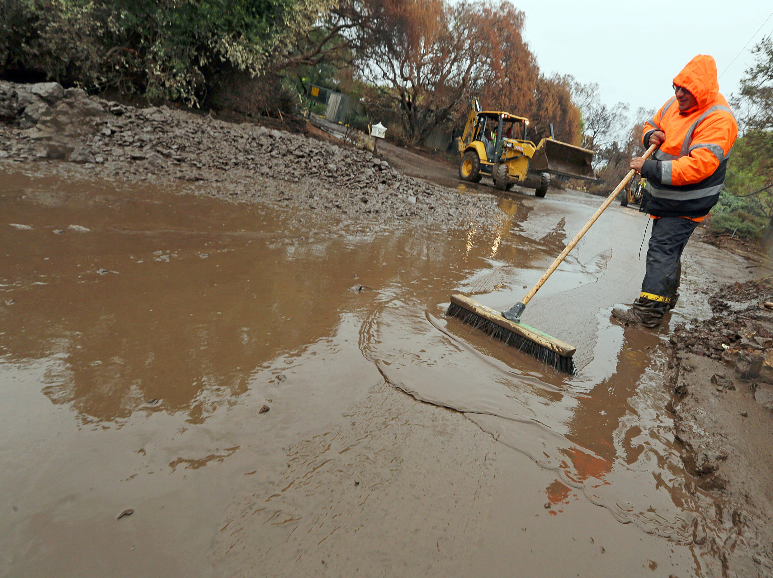 A Malibu Public Works crew clears a culvert that overflowed with mud and debris on Cuthbert Road in an area burned by the Woolsey fire in Malibu, Calif. Thursday, Dec. 6, 2018. The second round of a fall storm is causing flooding on Los Angeles-area roads. Snow has forced the closure of Interstate 5 in the Grapevine area between LA and the San Joaquin Valley. Closer to sea level, the system dumped rain that flooded highways and caused nightmare traffic conditions for commuters.