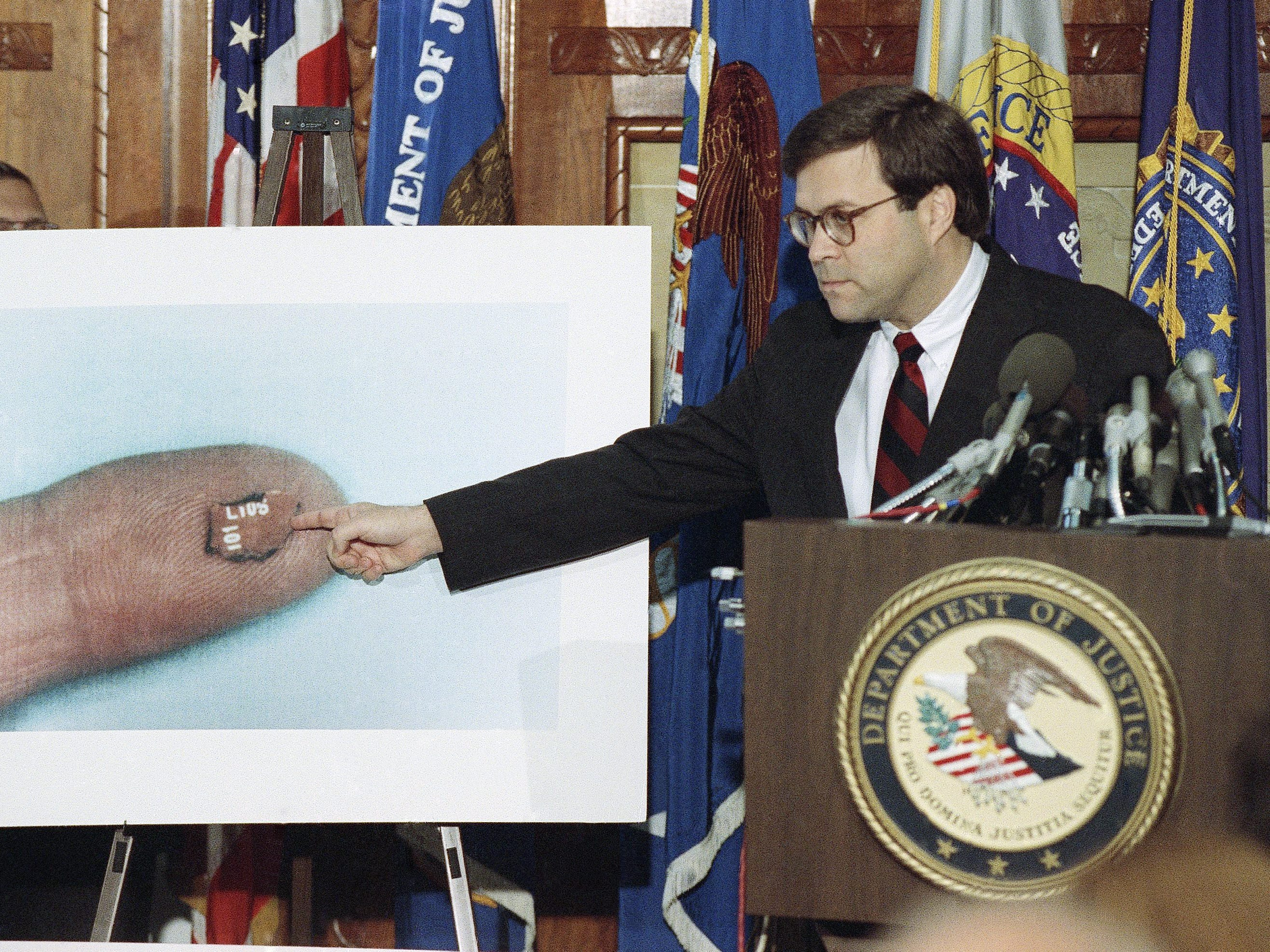 Acting U.S. Attorney General William Barr points to a fragment of a circuit board during a news conference on Pan Am Flight 103 in Washington, Thursday, Nov. 14, 1991. The tiny fragment was described as part of the bomb inside a portable radio. Two Libyan intelligence officials were indicted on Thursday in the bombing of the plane over Lockerbie, Scotland in 1988, which killed 270 people. (AP Photo/Barry Thumma)