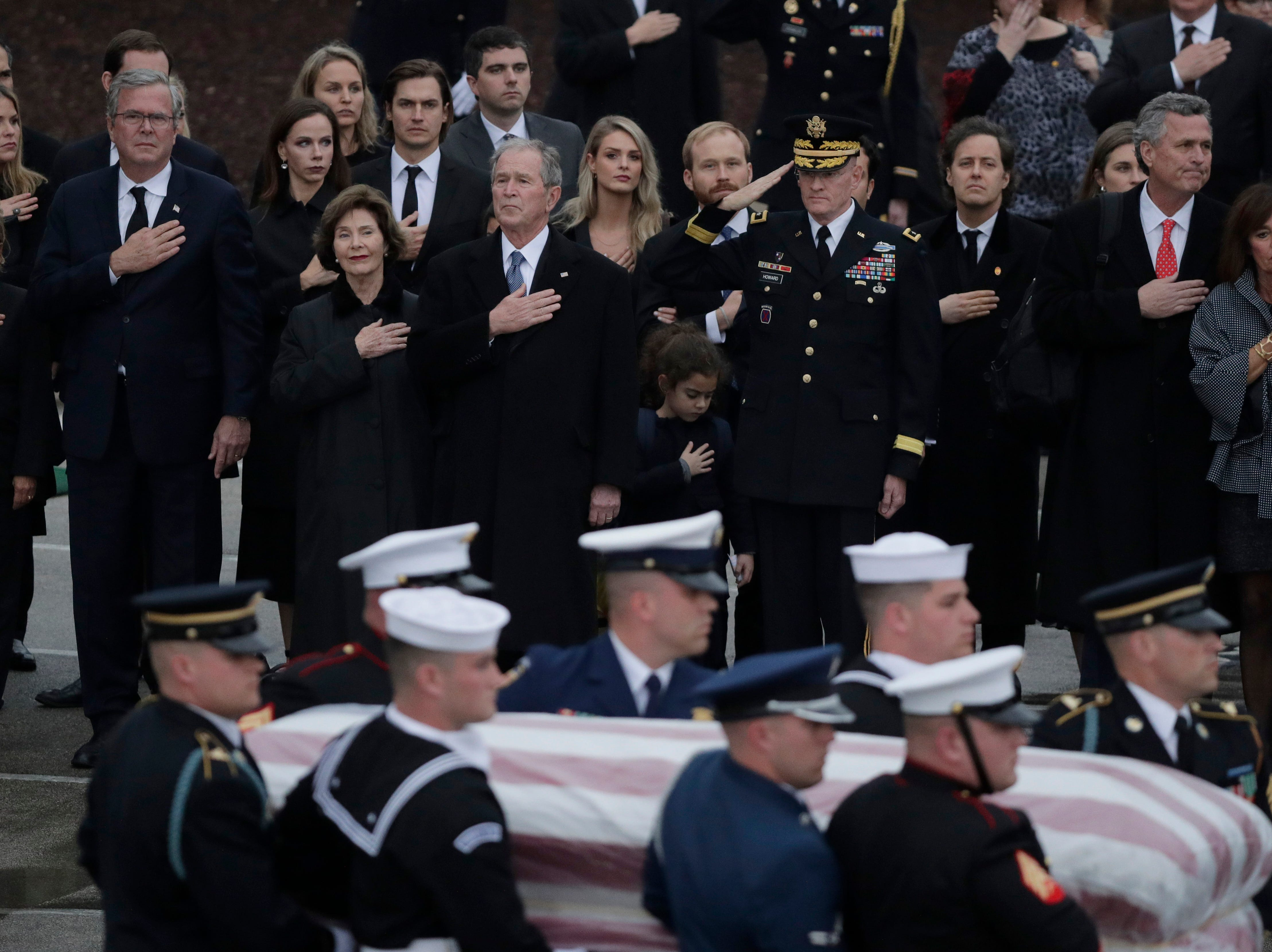 Former Florida Gov. Jeb Bush, second from left, with wife Columba, and former President George W. Bush, center, with wife Laura, and other family members, watch as the flag-draped casket of former President George H.W. Bush is carried by a joint services military honor guard after if arrived by train for burial at the George Bush Presidential Library, Thursday, Dec. 6, 2018, in College Station.
