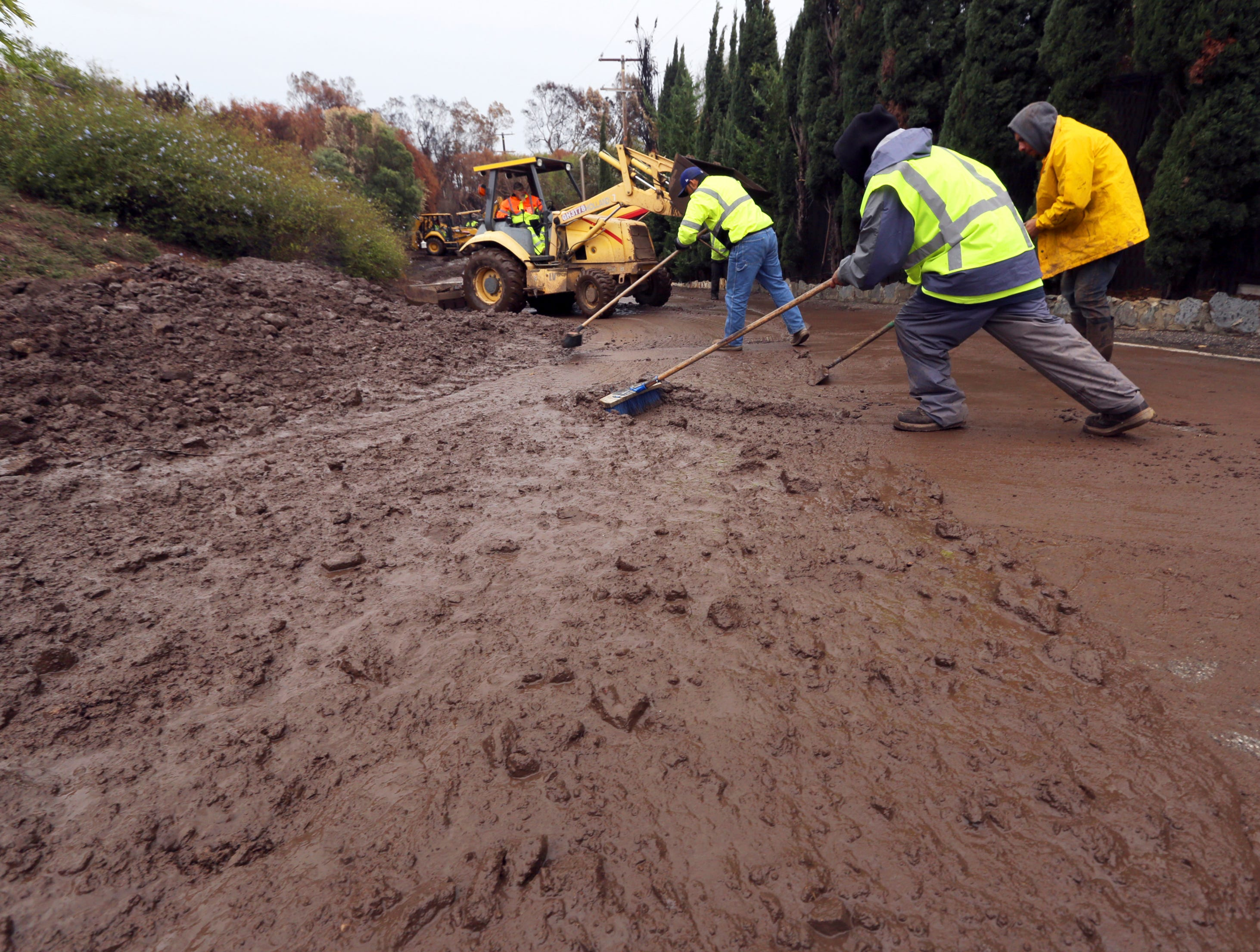 A Malibu Public Works crew clears a culvert on that overflowed with mud and debris on Cuthbert Road in an area burned by the Woolsey fire in Malibu, Calif. Thursday, Dec. 6, 2018.