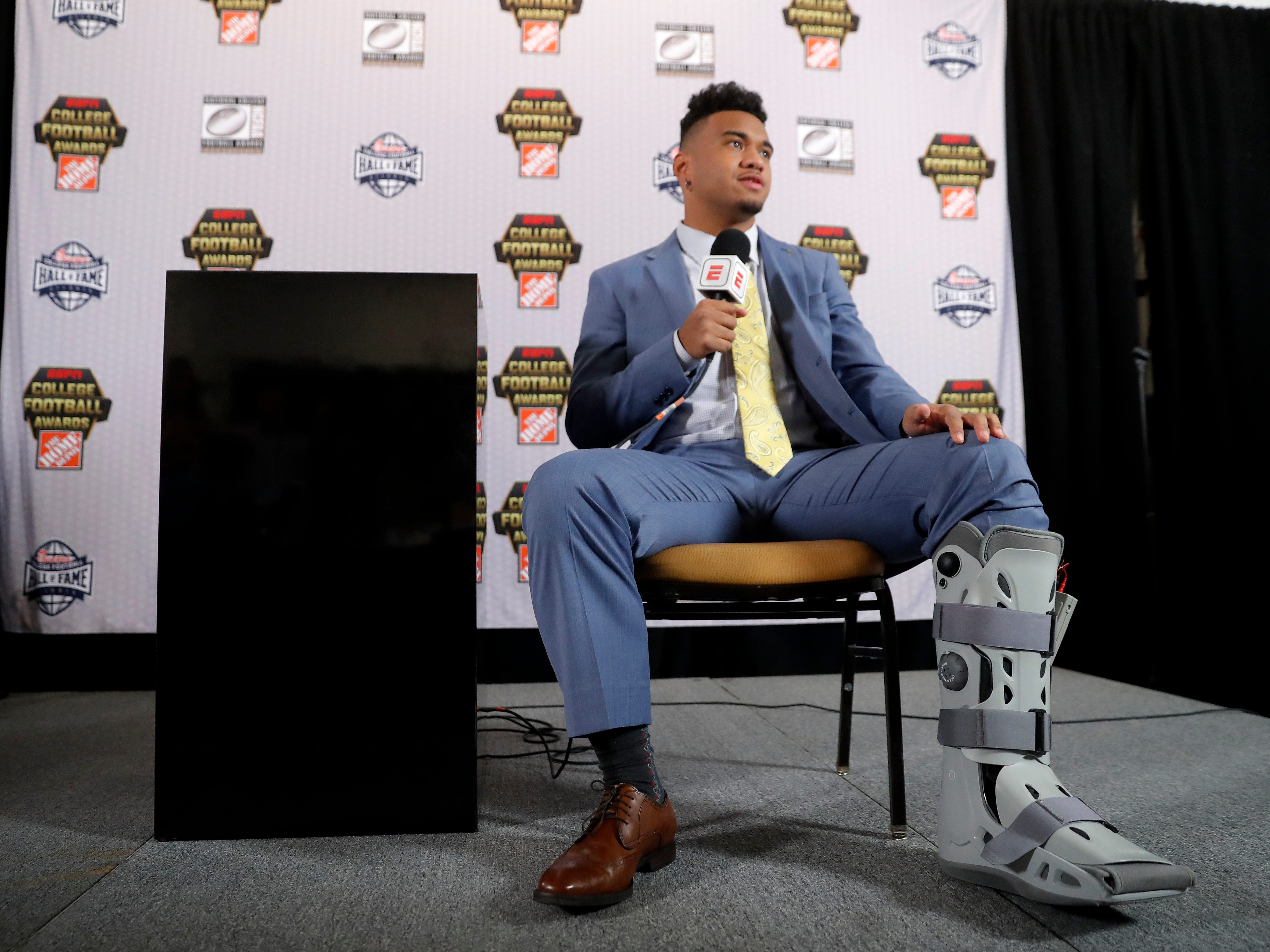 Alabama quarterback Tua Tagovailoa wears a protective boot on his injured foot as he speaks to reporters after winning the Maxwell Award and the Walter Camp honor. Tagovailoa was injured in the Southeast Conference championship game against Georgia.