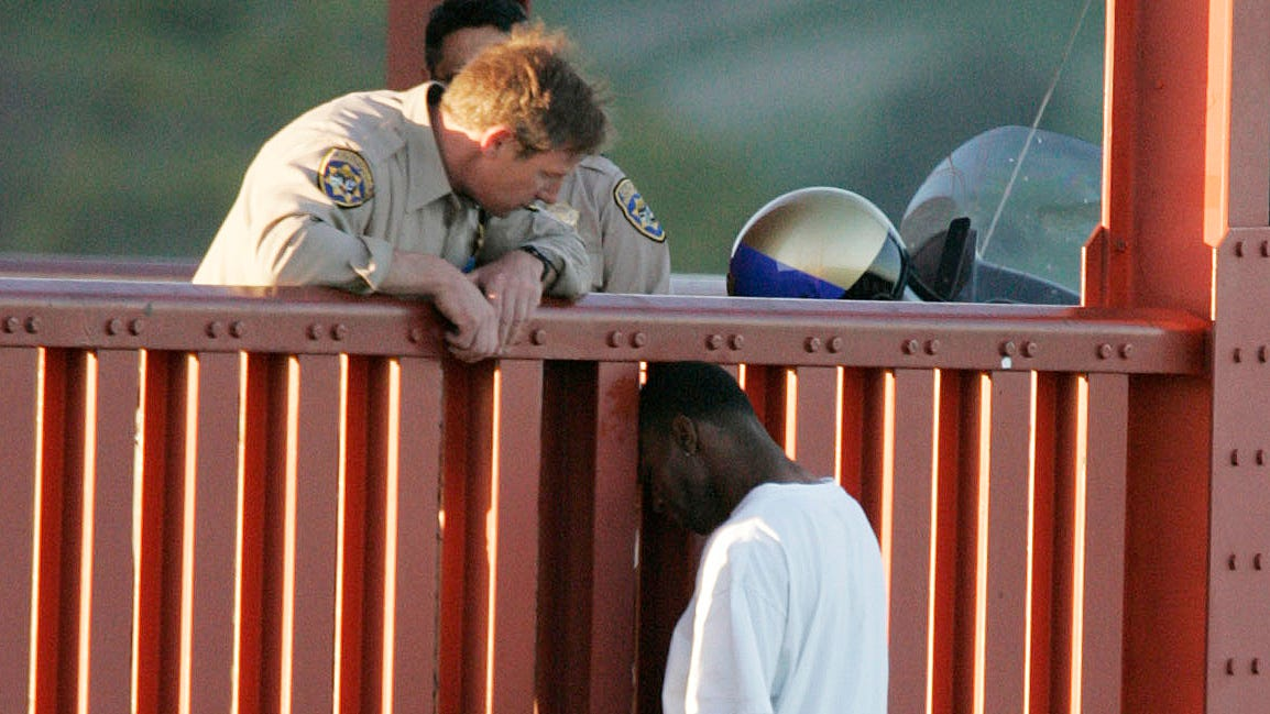 In this March 11, 2005 photo, Kevin Berthia is talked out of jumping off the Golden Gate Bridge by California Highway Patrolman Kevin Briggs in San Francisco.  During his 20 years patrolling the bridge Briggs has managed to talk may despondent people out of taking the fatal fall.