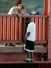 In this March 11, 2005, photo, Kevin Berthia is talked out of jumping off the Golden Gate Bridge by California Highway Patrolman Kevin Briggs in San Francisco. During his 20 years patrolling the bridge, Briggs has managed to talk many despondent people out of taking the fatal fall.
