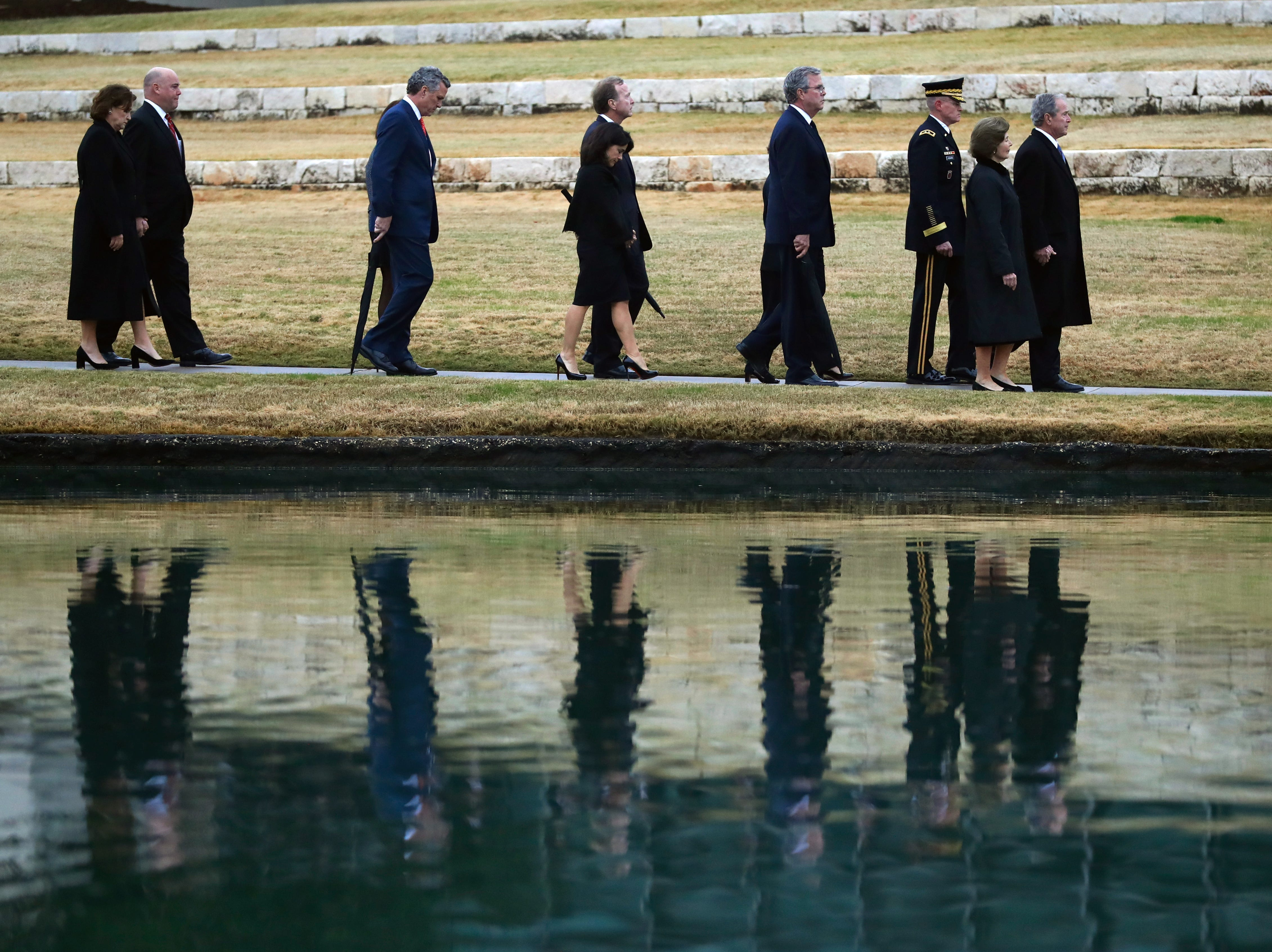 Family members follow the flag-draped casket of former President George H.W. Bush at the George H.W. Bush Presidential Library and Museum Thursday, Dec. 6, 2018, in College Station, Texas.