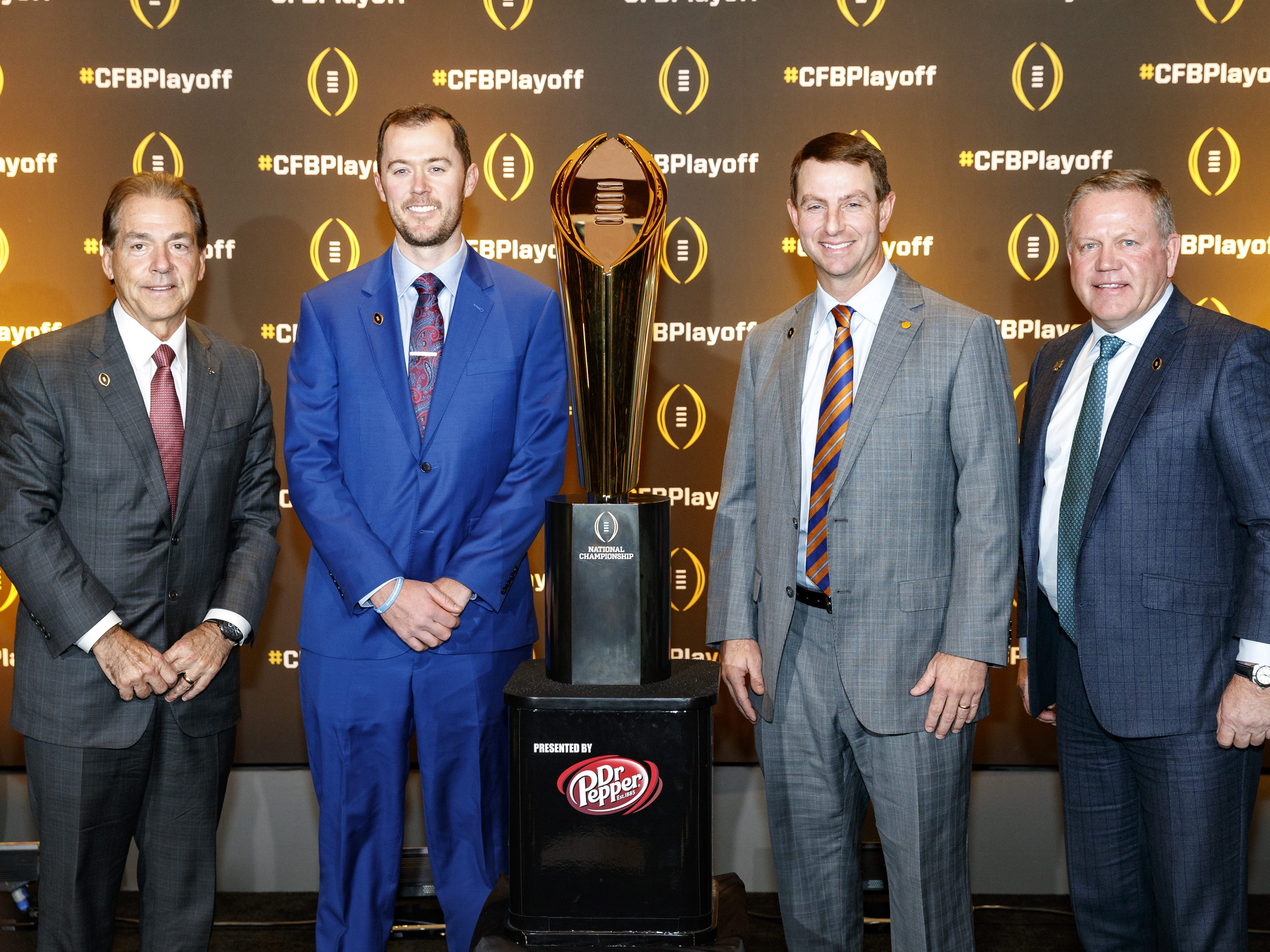 Alabama coach Nick Saban, Oklahoma coach Lincoln Riley, Clemson coach Dabo Swinney and Notre Dame coach Brian Kelly pose with the National Championship Trophy at the College Football Playoff Semifinal Head Coaches News Conference in Atlanta.