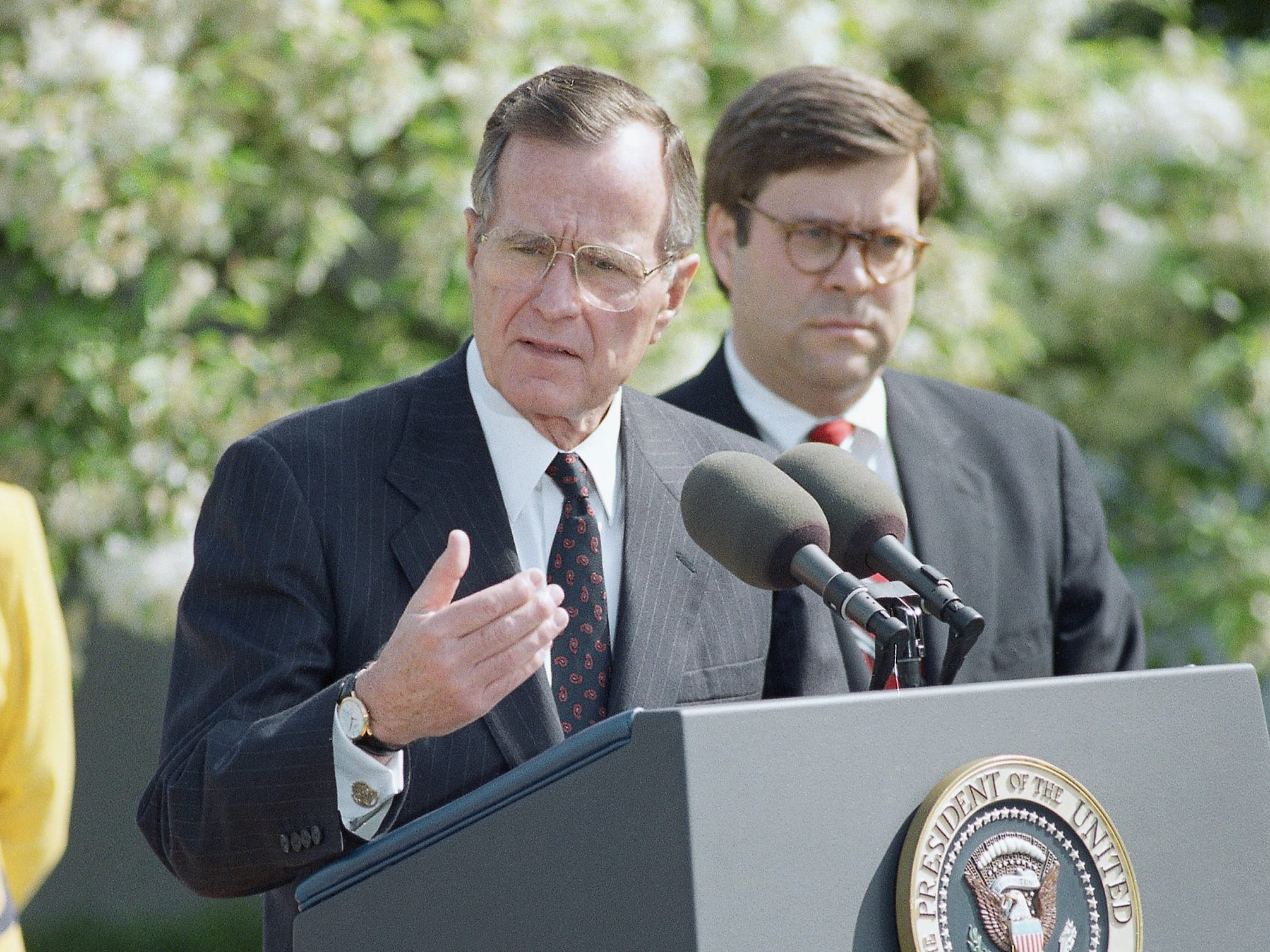 U.S. President George H. Bush gestures during an address in the Rose Garden of the White House in Washington, Friday, April 24, 1992 honoring the National Crime Victims Rights Award winners. Attorney General William Barr looks on at right. Each year the Justice department awards those individuals who have worked on behalf of crime victims and honors the accomplishments of the Victims of Crime Act passed in 1984. (AP Photo/J. Scott Applewhite)