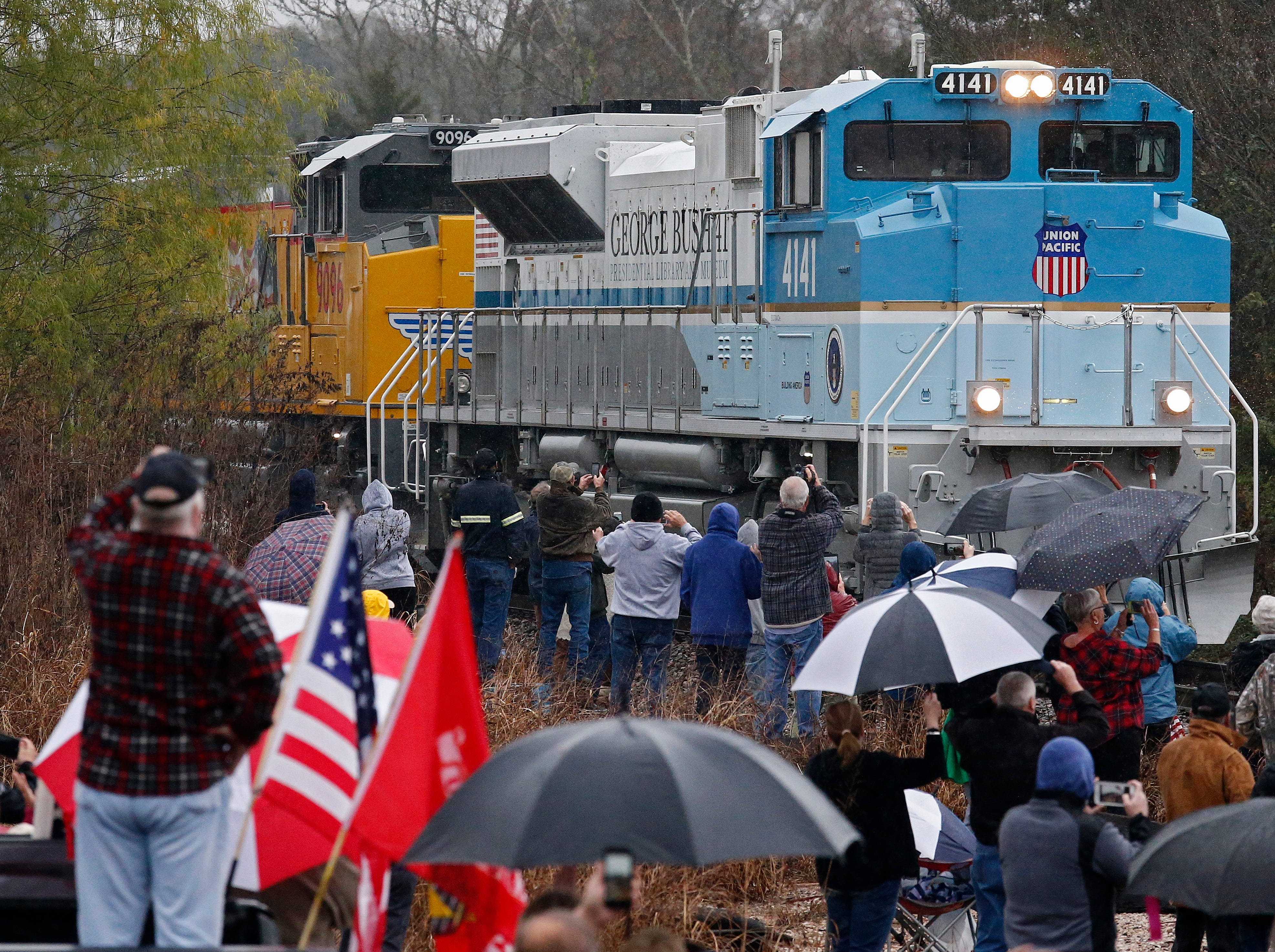 People watch as the train carrying the casket of former President George H.W. Bush passes by in the country near Millican, Texas on Dec. 6, 2018.